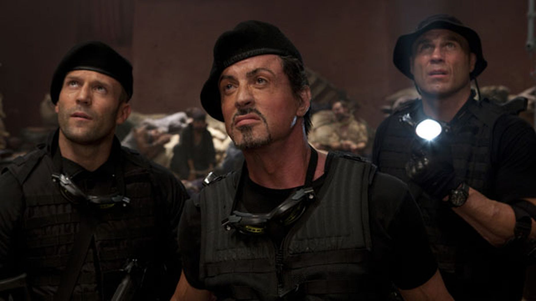 """In this film publicity image released by Lionsgate Entertainment, from left, Jason Statham, Sylvester Stallone and Randy Couture are shown in a scene from """"The Expendables."""""""