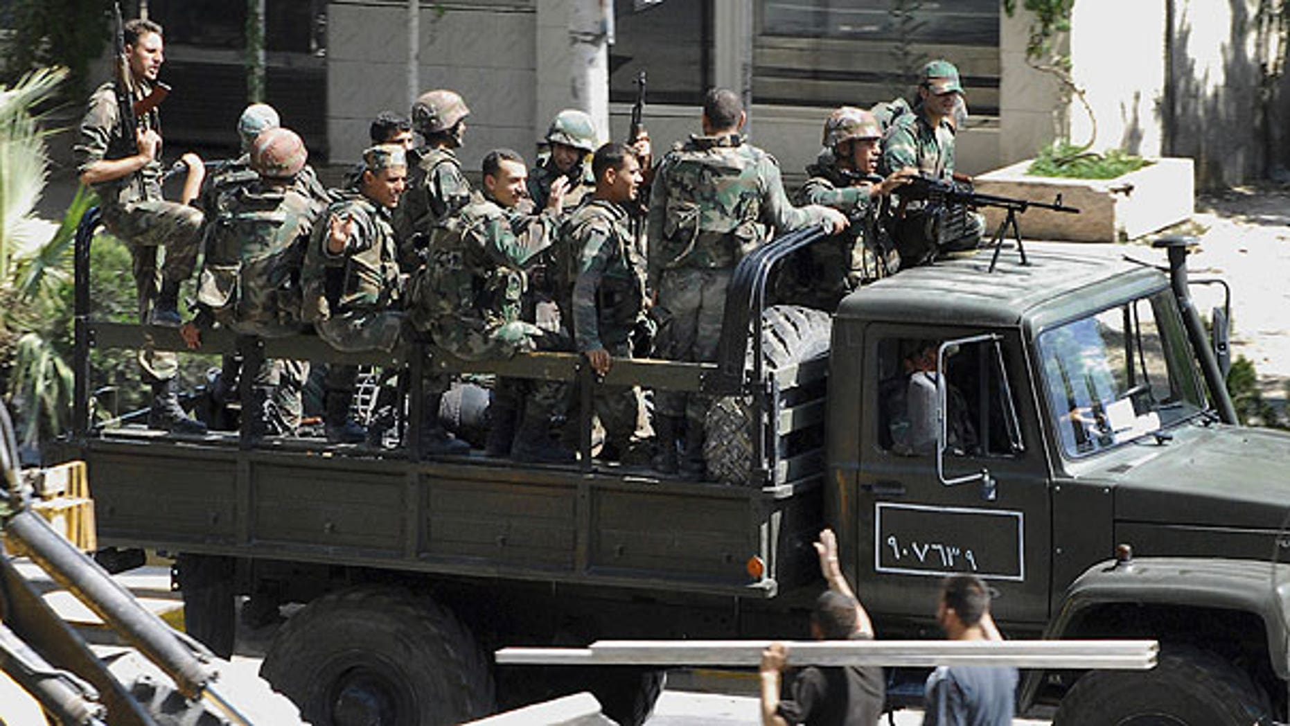 Aug. 14: In this citizen journalism image, Syrian citizens, below right, wave to Syrian troops who withdraw from the Damascus suburb of Saqba, Syria, following a campaign of raids and arrests that started overnight and continued Sunday morning.