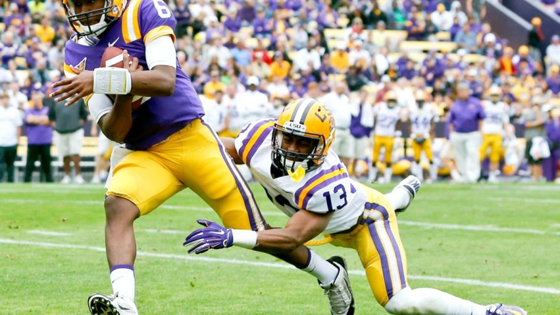 Apr 5, 2014; Baton Rouge, LA, USA; LSU Tigers quarterback Brandon Harris (6) runs for a touchdown past cornerback Dwayne Thomas (13) during the 2014 spring game at Tiger Stadium. Mandatory Credit: Derick E. Hingle-USA TODAY Sports