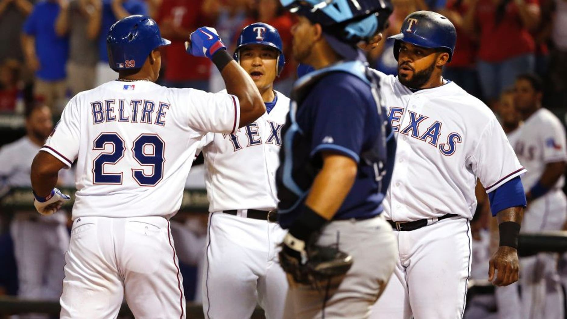 Texas Rangers third baseman Adrian Beltre (29) celebrates with teammates Shin-Soo Choo, center, and Prince Fielder after his three-run home run, while Tampa Bay Rays catcher Rene Rivera stands nearby during the sixth inning of a baseball game Saturday, Aug. 15, 2015, in Arlington, Texas. The Rangers defeated the Rays 12-4. (AP Photo/Ron Jenkins)