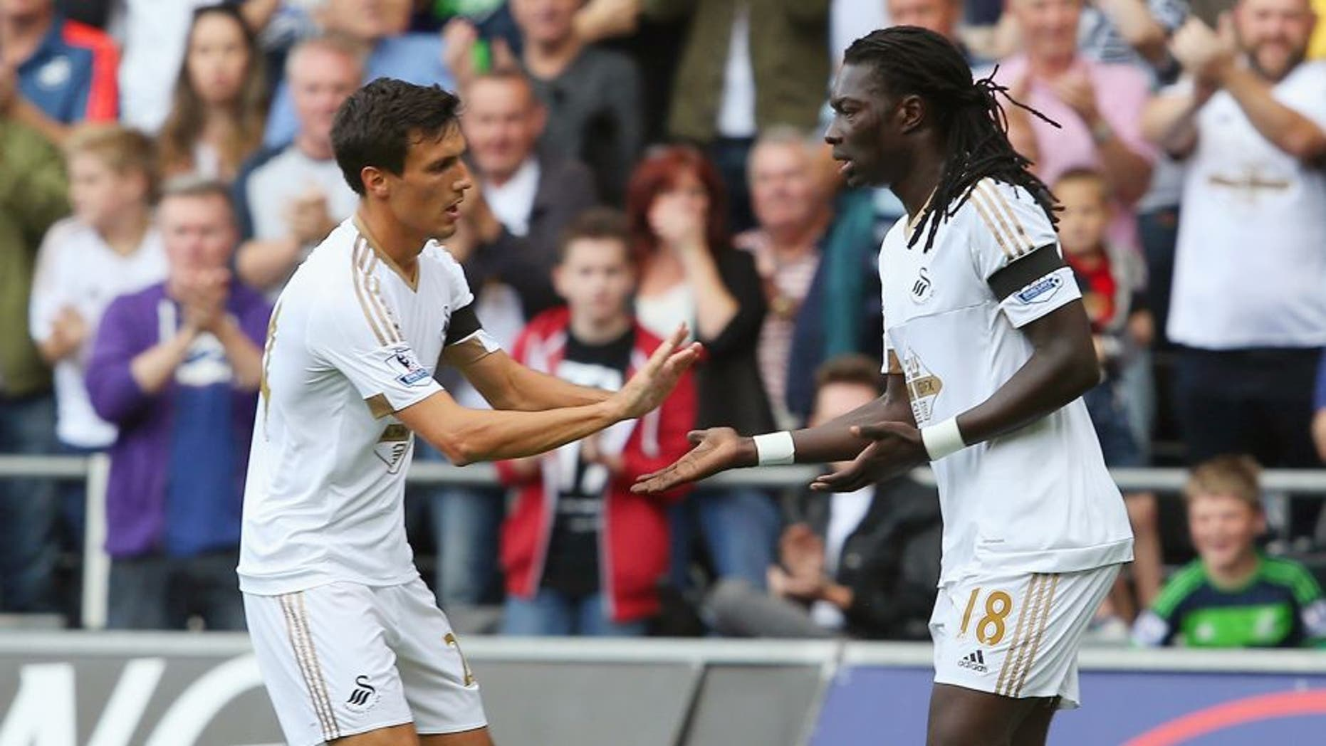 SWANSEA, WALES - AUGUST 15: Bafetimbi Gomis of Swansea City celebrates scoring his team's first goal with his team mate Jack Cork during the Barclays Premier League match between Swansea City and Newcastle United at Liberty Stadium on August 15, 2015 in Swansea, United Kingdom. (Photo by Jan Kruger/Getty Images)