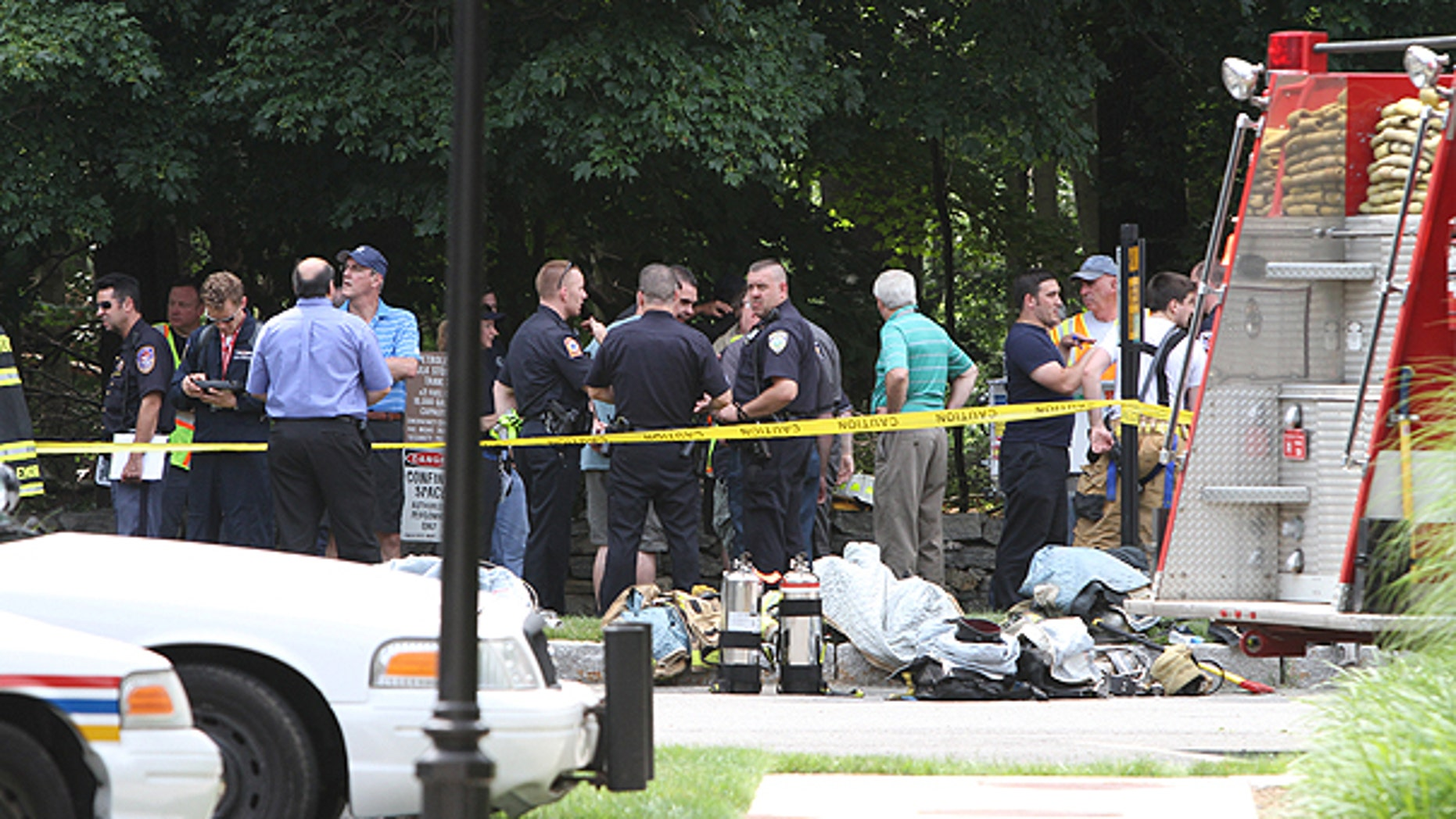 June 18: Various police and fire agencies work at the nearby wreckage site of a small plane crash in Armonk, N.Y.