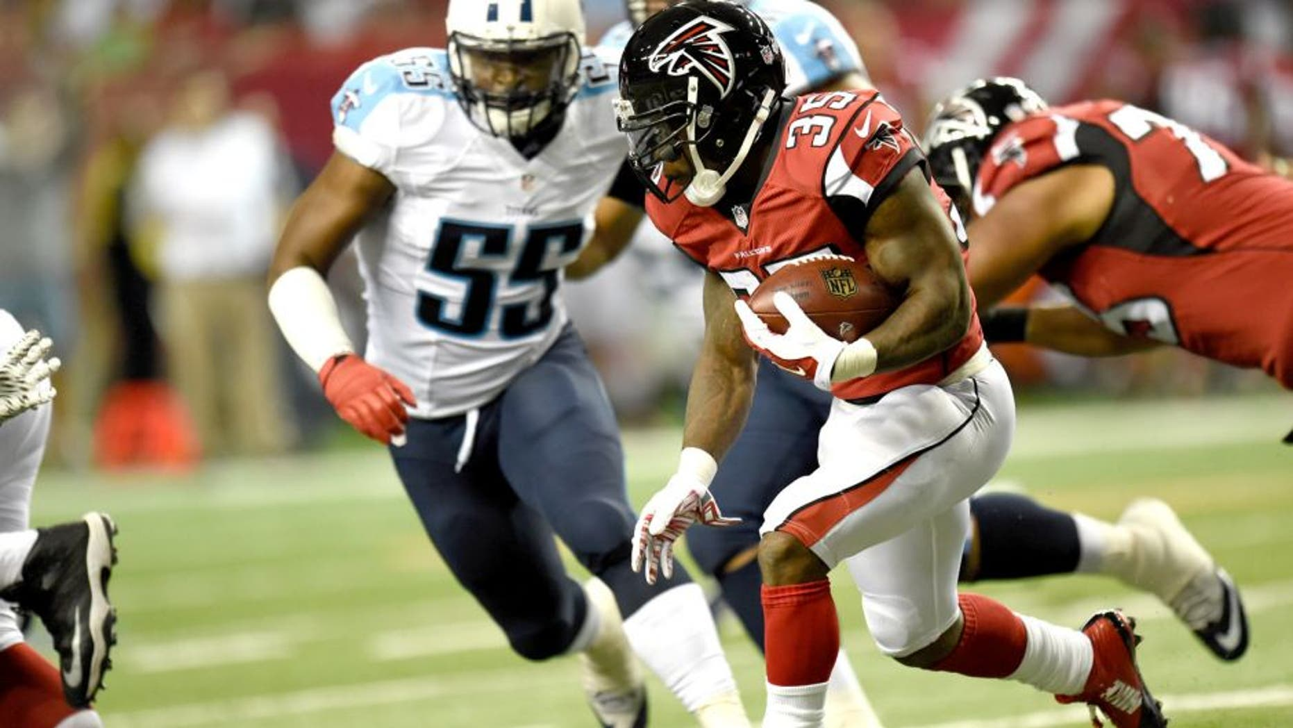 Aug 14, 2015; Atlanta, GA, USA; Atlanta Falcons running back Antone Smith (35) runs past Tennessee Titans linebacker Zach Brown (55) during the first half at the Georgia Dome. The Falcons defeated the Titans 31-24. Mandatory Credit: Dale Zanine-USA TODAY Sports
