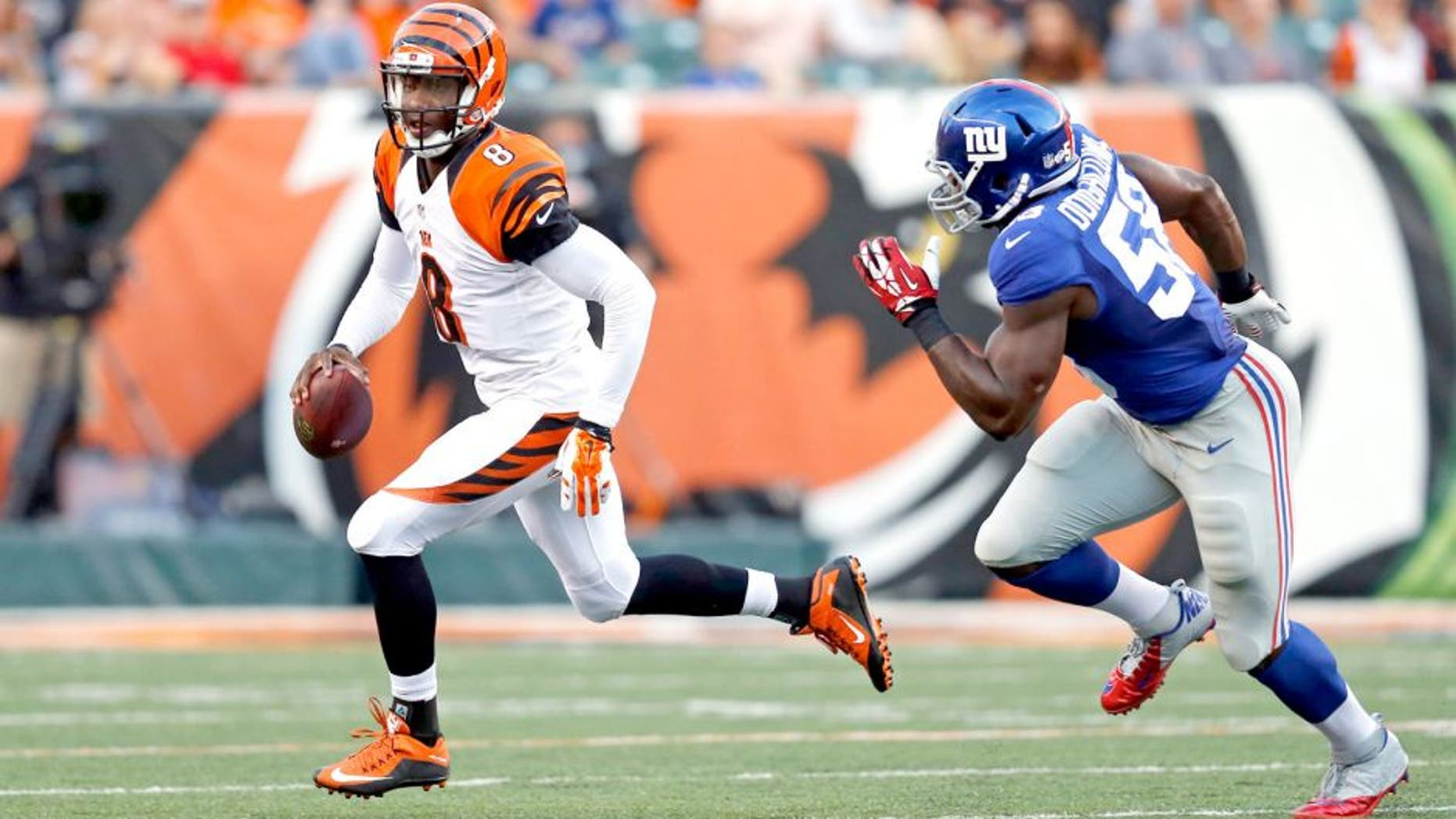 New York Giants defensive end Owamagbe Odighizuwa (58) chases Cincinnati Bengals quarterback Josh Johnson during the first half of an NFL preseason football game in Cincinnati, Friday, Aug. 14, 2015. (AP Photo/Gary Landers)
