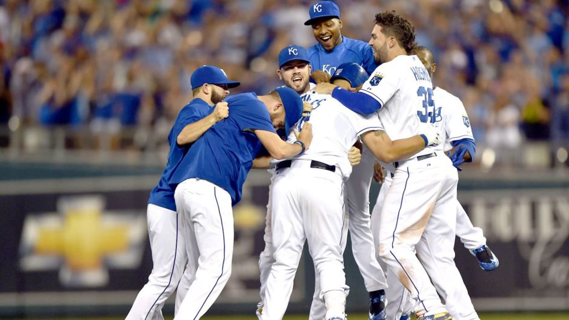 Aug 16, 2015; Kansas City, MO, USA; Kansas City Royals players celebrate after Kendrys Morales (center) hit a walk off single against the Los Angeles Angels during the tenth inning at Kauffman Stadium. Mandatory Credit: Peter G. Aiken-USA TODAY Sports