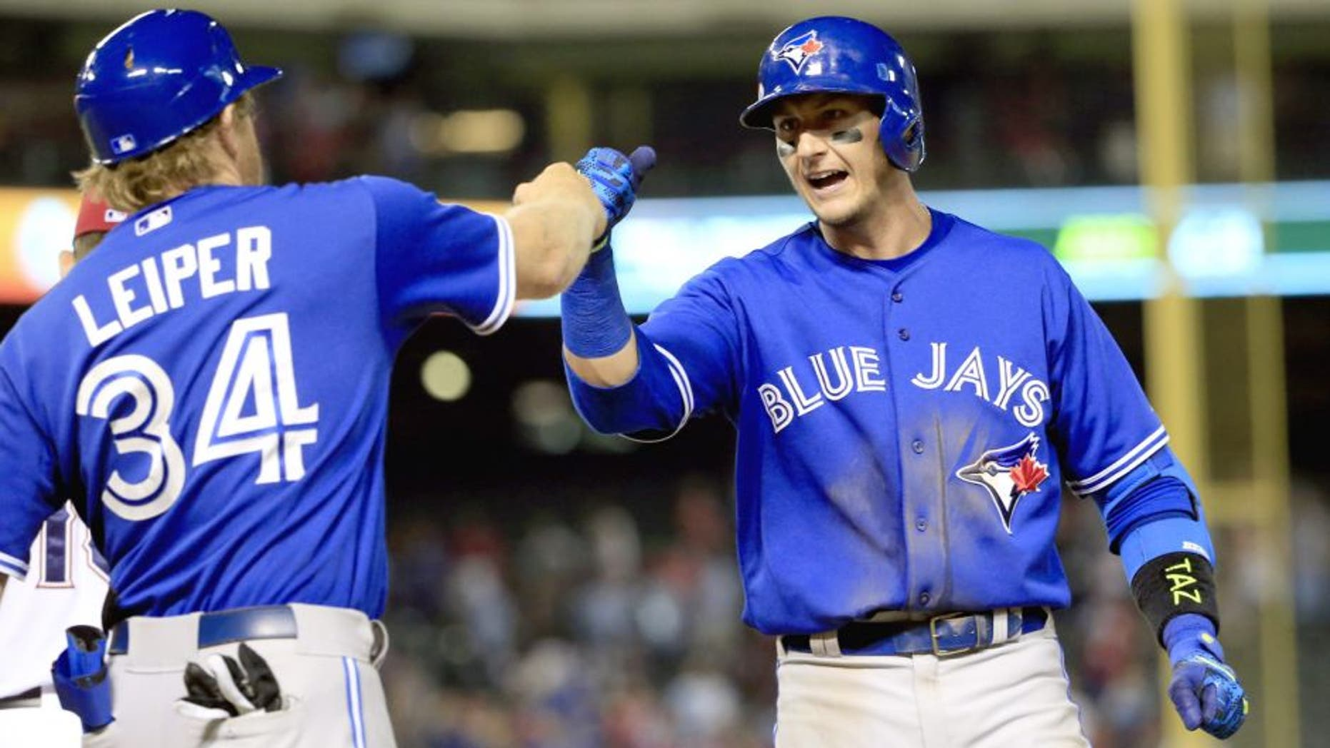 Aug 25, 2015; Arlington, TX, USA; Toronto Blue Jays shortstop Troy Tulowitzki (2) celebrates with first base coach Tim Leiper (34) after hitting the game tying single against the Texas Rangers during the ninth inning at Globe Life Park in Arlington. Mandatory Credit: Kevin Jairaj-USA TODAY Sports