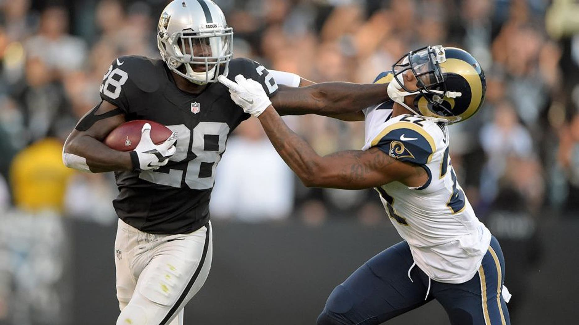Aug 14, 2015; Oakland, CA, USA; Oakland Raiders running back Latavius Murray (28) stiff arms St. Louis Rams corneramback Tremaine Johnson (22) in a preseason NFL football game at O.co Coliseum. Mandatory Credit: Kirby Lee-USA TODAY Sports