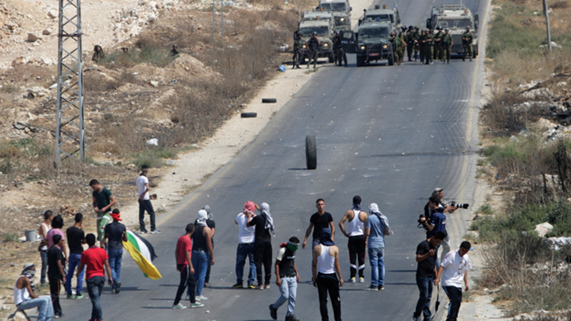 August 15, 2014: Palestinian protesters face Israeli soldiers during clashes near the West Bank city of Nablus. (AP)