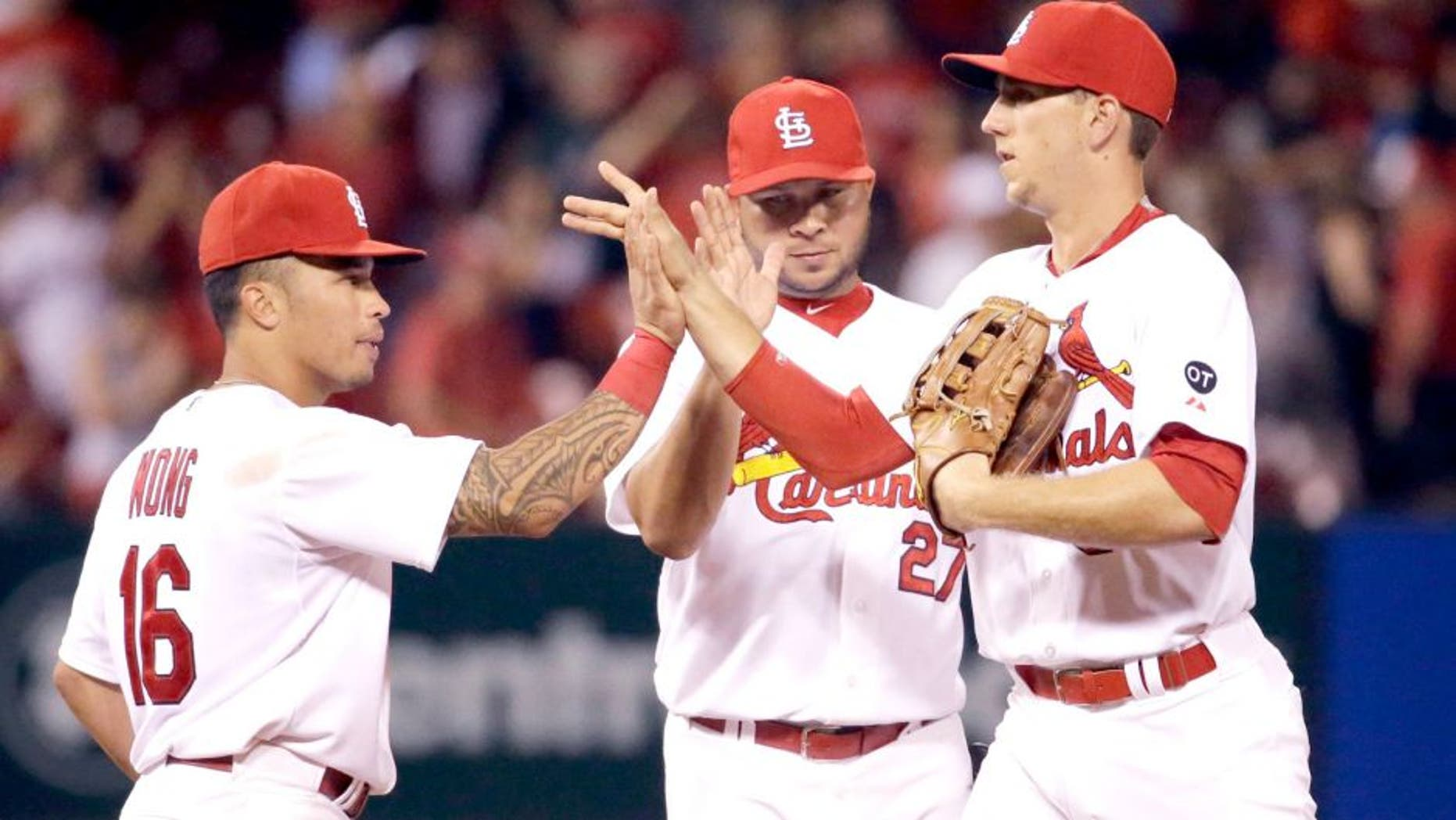 St. Louis Cardinals, from left to right, Kolten Wong, Jhonny Peralta and Stephen Piscotty celebrate following the Cardinals' 2-1 victory over the San Francisco Giants in a baseball game Monday, Aug. 17, 2015, in St. Louis. (AP Photo/Jeff Roberson)