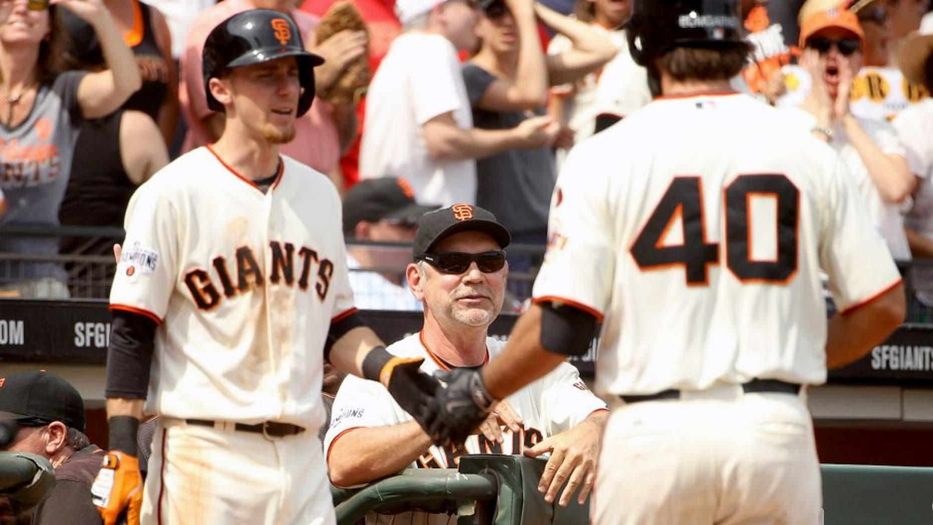 SAN FRANCISCO, CA - AUGUST 16: Manager Bruce Bochy smiles as Matt Duffy #5 congratulates Madison Bumgarner #40 of the San Francisco Giants after Bumgarner hit a home run in the seventh inning against the Washington Nationals at AT&T Park on August 16, 2015 in San Francisco, California. (Photo by Ezra Shaw/Getty Images)