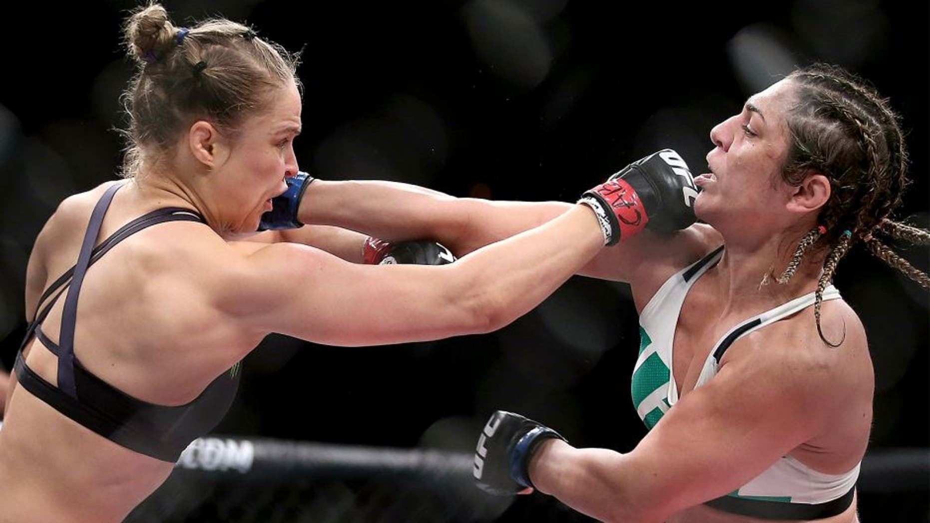 RIO DE JANEIRO, BRAZIL - AUGUST 01: Ronda Rousey of the United States (red) fights Bethe Correia of Brazi (blue) l in their bantamweight title fight during the UFC 190 Rousey v Correia at HSBC Arena on August 1, 2015 in Rio de Janeiro, Brazil. (Photo by Matthew Stockman/Getty Images)