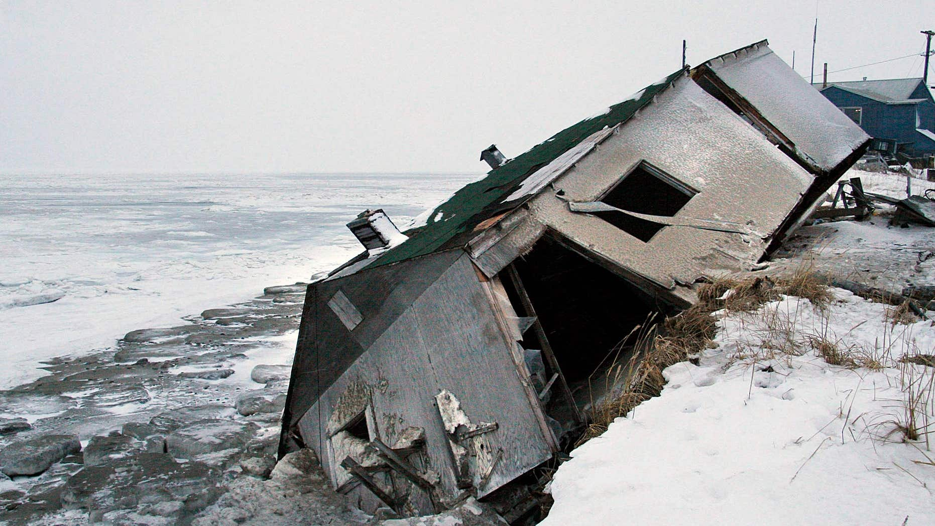 FILE - In this Dec. 8, 2006, file photo, Nathan Weyiouanna's abandoned house at the west end of Shishmaref, Alaska, sits on the beach after sliding off during a fall storm in 2005.