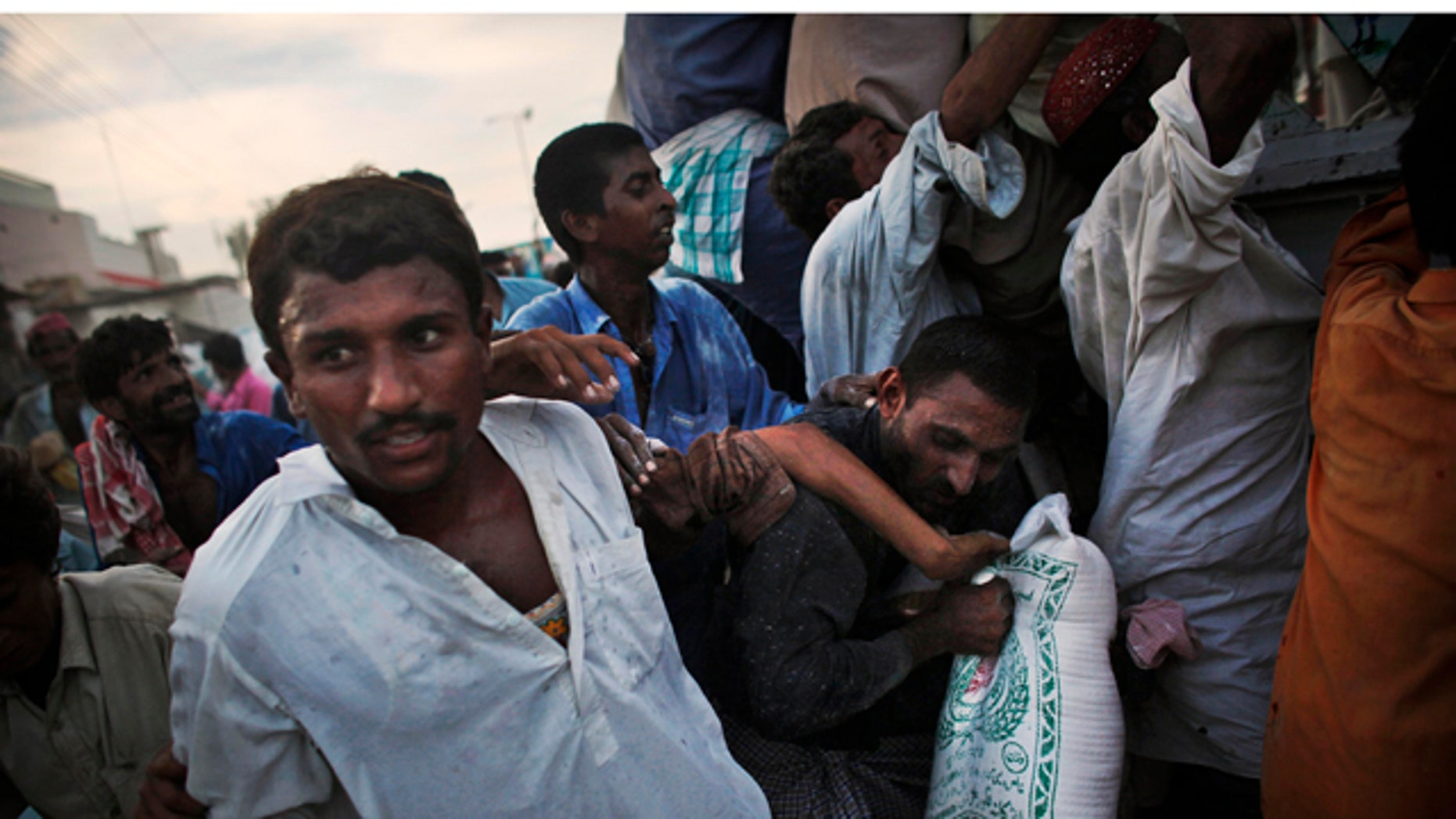 Aug. 17: Pakistanis displaced by flooding grab a bag of food aid as they crowd during a distribution on the road near the flood line outside of Sukkur, in Sindh province, southern Pakistan.