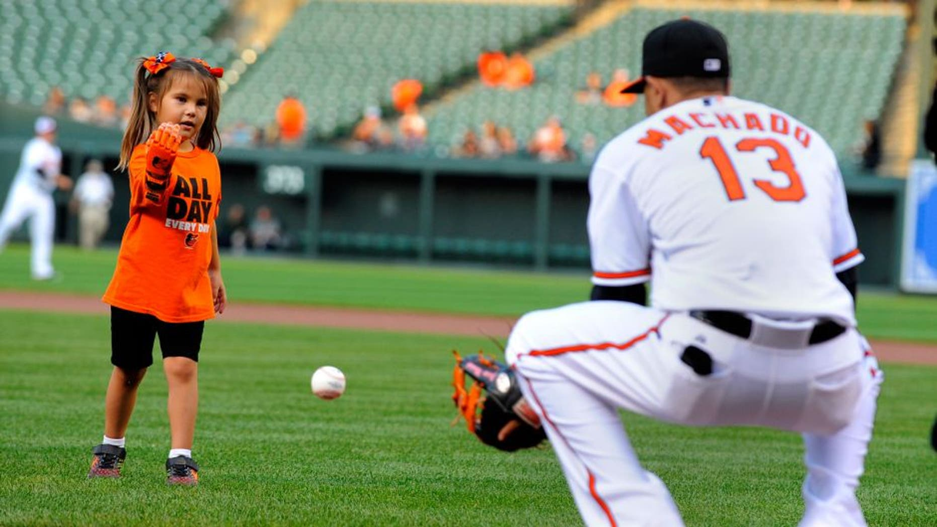 """Hailey Dawson, a 5-year-old from Las Vegas, throws the ceremonial first pitch before a game between the Baltimore Orioles and Oakland Athletics on Monday, Aug. 17, 2015, at Camden Yards in Baltimore. Hailey was born with Poland Syndrome. Engineering students at the University of Nevada, Las Vegas created the """"Flexy Hand 2"""" that she wore to throw the ball. (Lloyd Fox/Baltimore Sun/TNS via Getty Images)"""