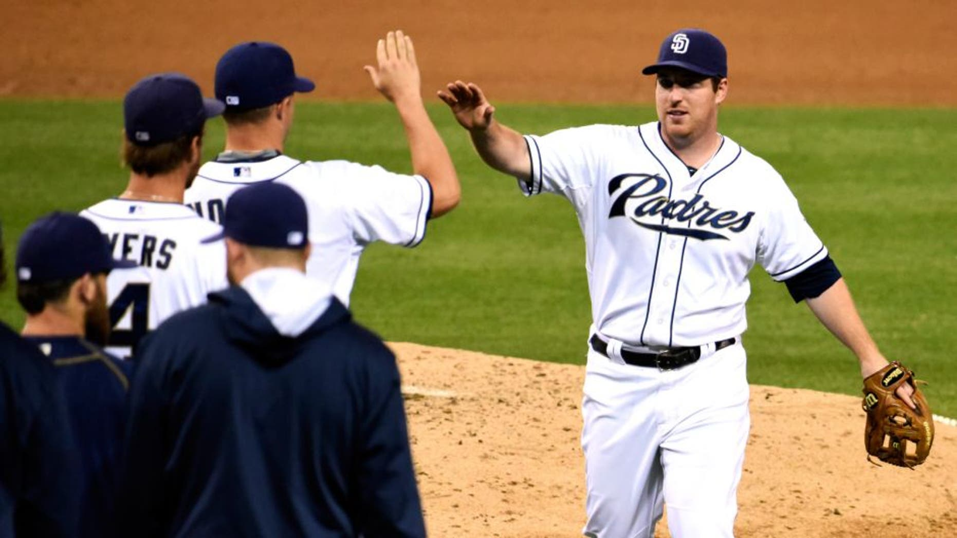 SAN DIEGO, CA - AUGUST 11: Jedd Gyorko #9 of the San Diego Padres, right, high-fives teammates after the Padres beat the Cincinnati Reds 11-6 in a baseball game at Petco Park August 11, 2015 in San Diego, California. (Photo by Denis Poroy/Getty Images)
