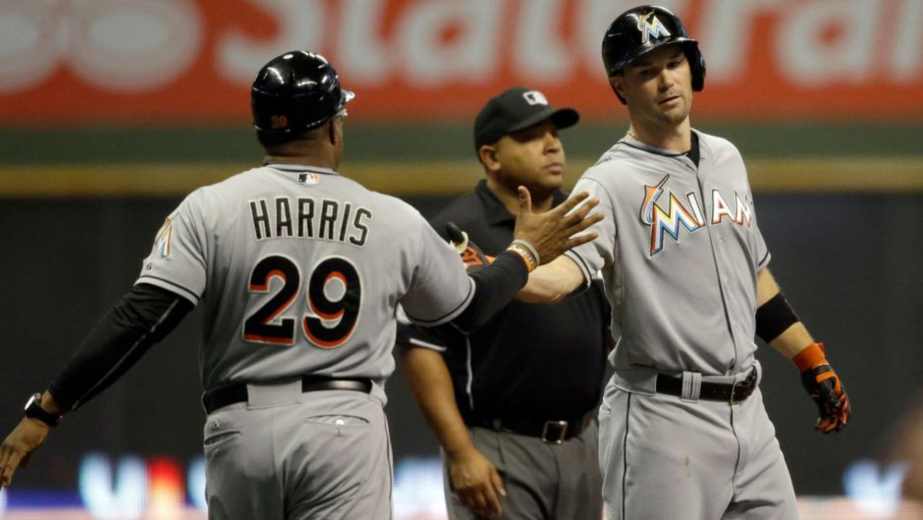 Miami Marlins' Cole Gillespie, right, is congratulated by third base coach Lenny Harris after Gillespie's three- run triple against the Milwaukee Brewers during the first inning of a baseball game, Tuesday, Aug. 18, 2015, in Milwaukee. (AP Photo/Jeffrey Phelps)