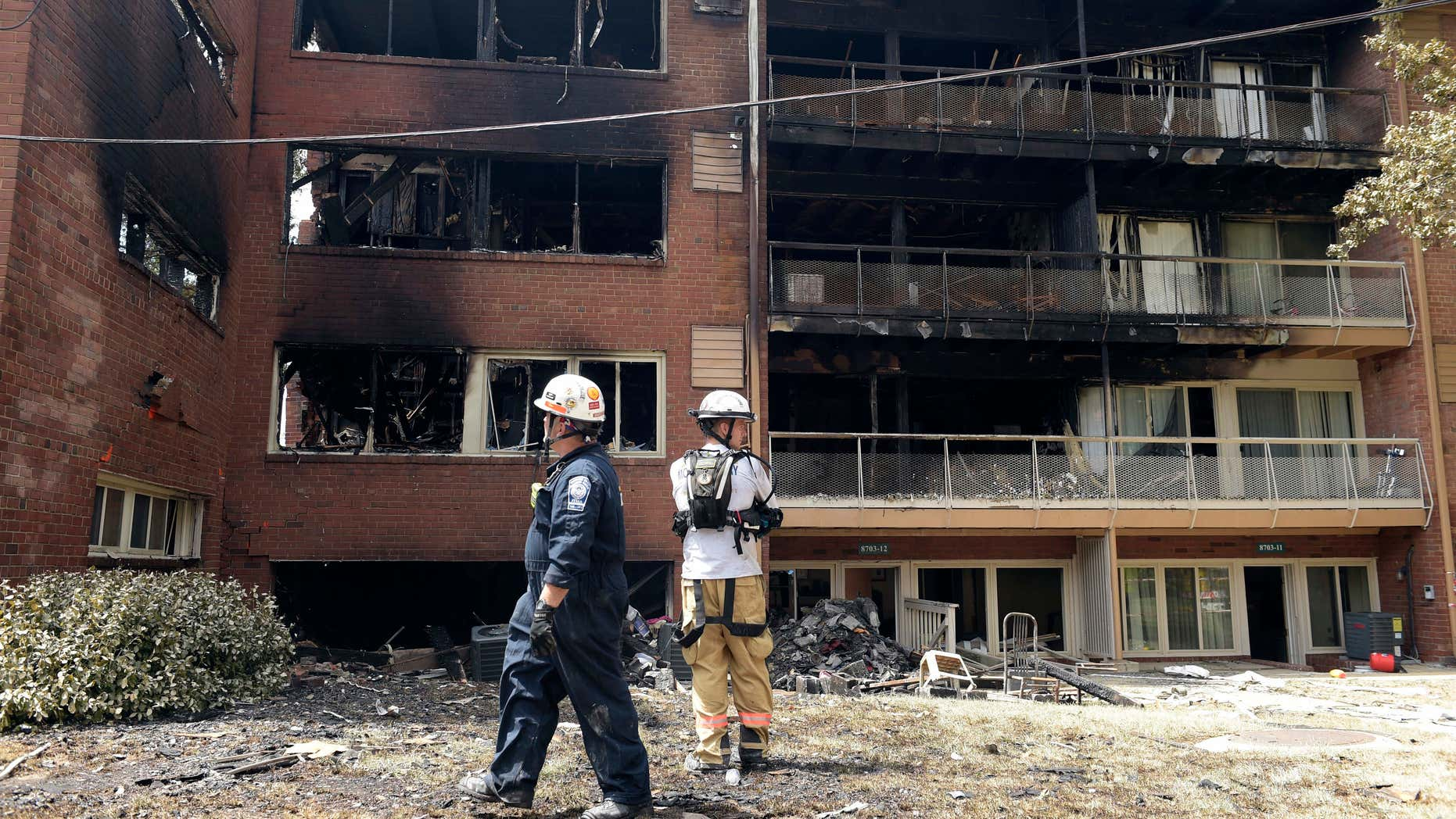 FILE - In this Thursday, Aug. 11, 2016, file photo, emergency personnel view the scene of an apartment building fire in Silver Spring, Md.