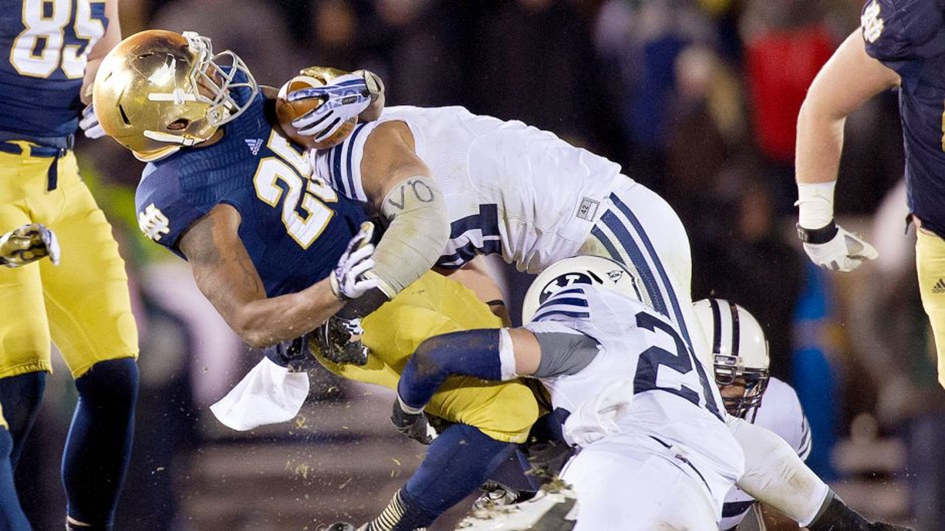 Nov 23, 2013; South Bend, IN, USA; Notre Dame Fighting Irish running back Tarean Folston (25) is tackled by BYU Cougars linebacker Uani 'Unga (41) and safety Craig Bills (20) in the third quarter at Notre Dame Stadium. Notre Dame won 23-13. Mandatory Credit: Matt Cashore-USA TODAY Sports