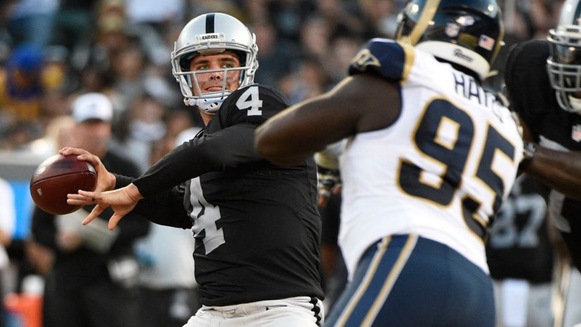 August 14, 2015; Oakland, CA, USA; Oakland Raiders quarterback Derek Carr (4) passes the football against St. Louis Rams defensive end William Hayes (95) during the first quarter in a preseason NFL football game at O.co Coliseum. Mandatory Credit: Kyle Terada-USA TODAY Sports