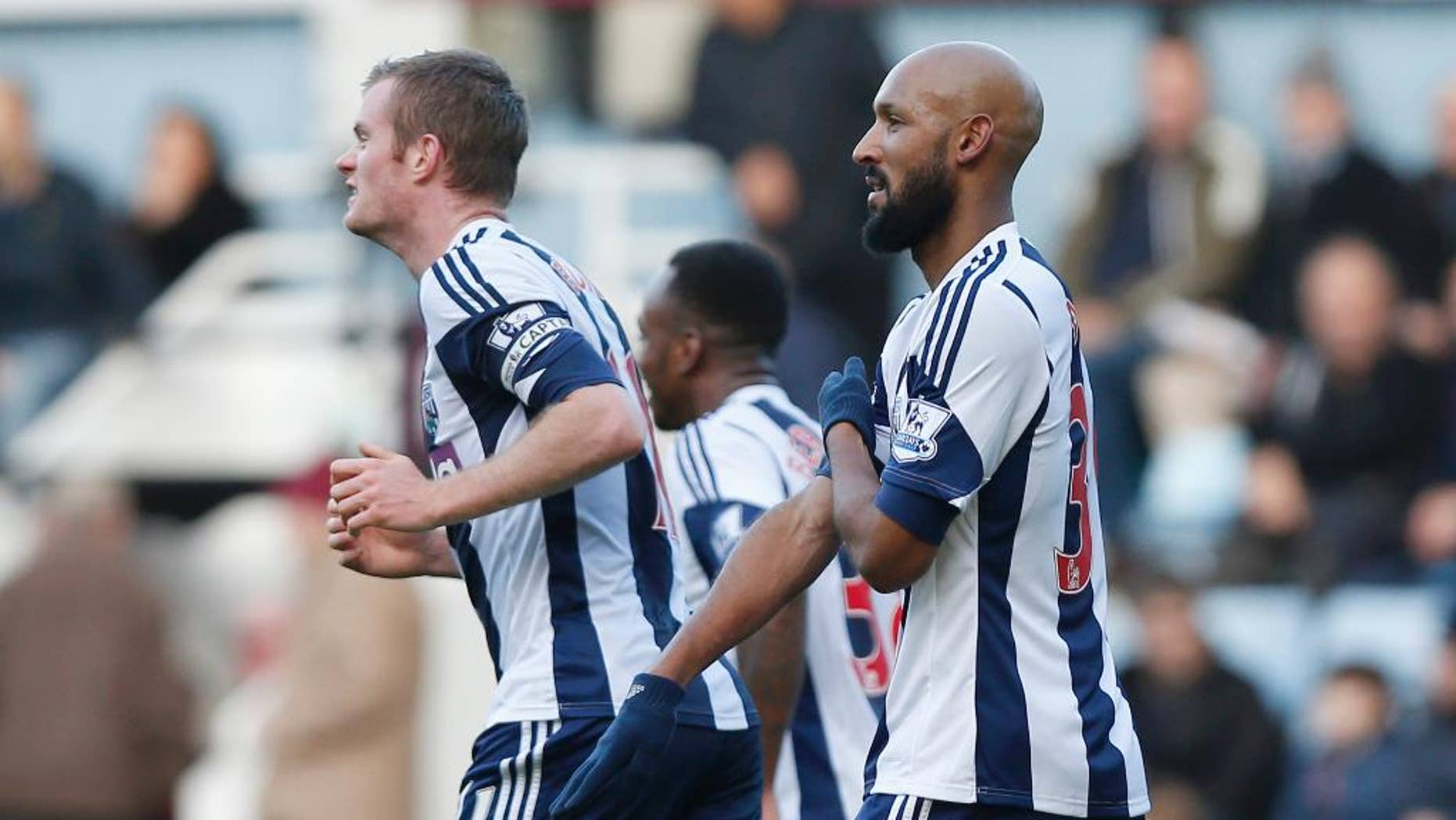 """FILE - In this Saturday, Dec. 28, 2013, file photo, West Bromwich Albion's Nicolas Anelka, right, gestures as he celebrates his goal against West Ham United during their English Premier League soccer match at Upton Park, London.  Anelka, was without a club since West Bromwich said it fired him in March 2014 following a five-match suspension for the racially aggravated goal celebration.  Former France striker Nicolas Anelka says he is joining Mumbai City FC in the new Indian Super League.The 35-year-old Anelka tweeted Monday Sept 15, 2014 """"I'm pleased to join Mumbai City FC & very exciting in joining Indian Super League."""" (AP Photo/Sang Tan, File)"""