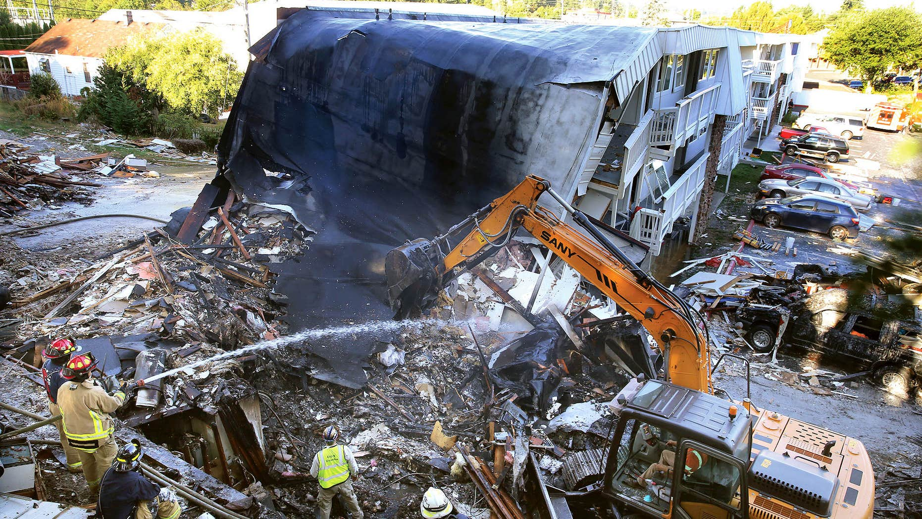 Aug. 19, 2015: Firefighters hose down the debris field from the collapsed east side of the Bremerton Motel 6.