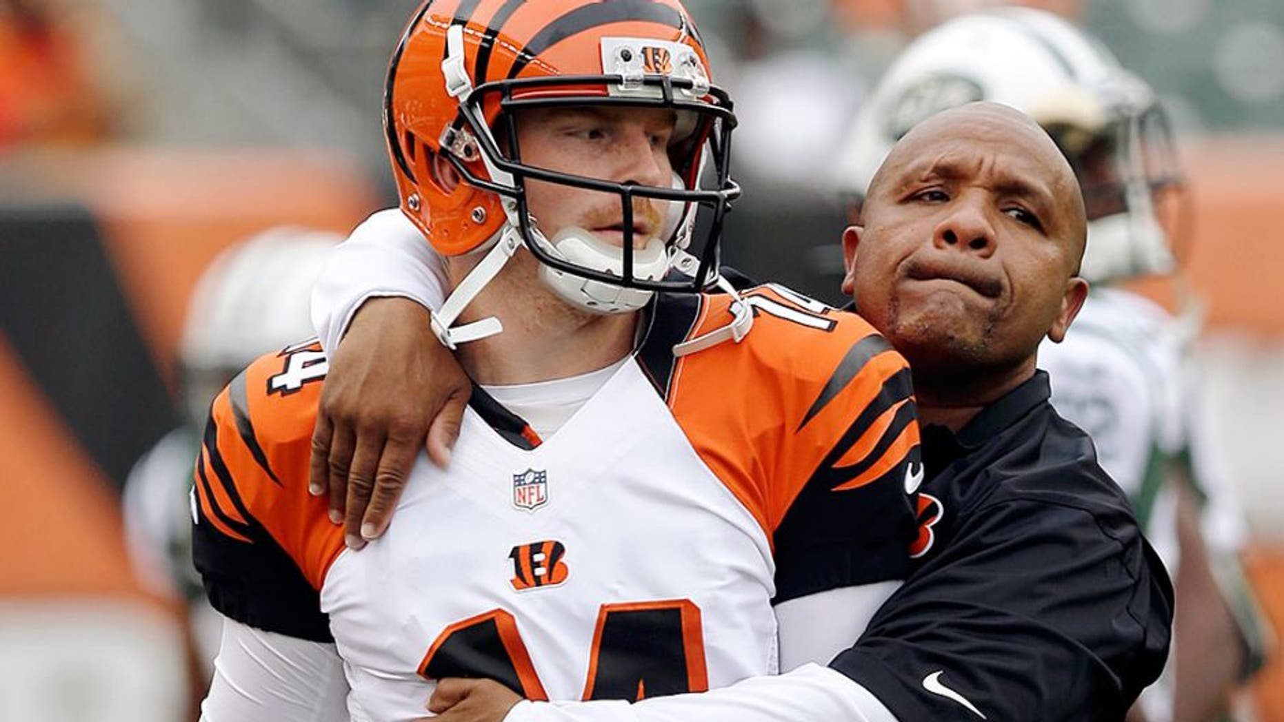 Cincinnati Bengals offensive coordinator Hue Jackson hugs quarterback Andy Dalton (14) prior to an NFL preseason football game against the New York Jets, Saturday, Aug. 16, 2014, in Cincinnati. (AP Photo/Al Behrman)