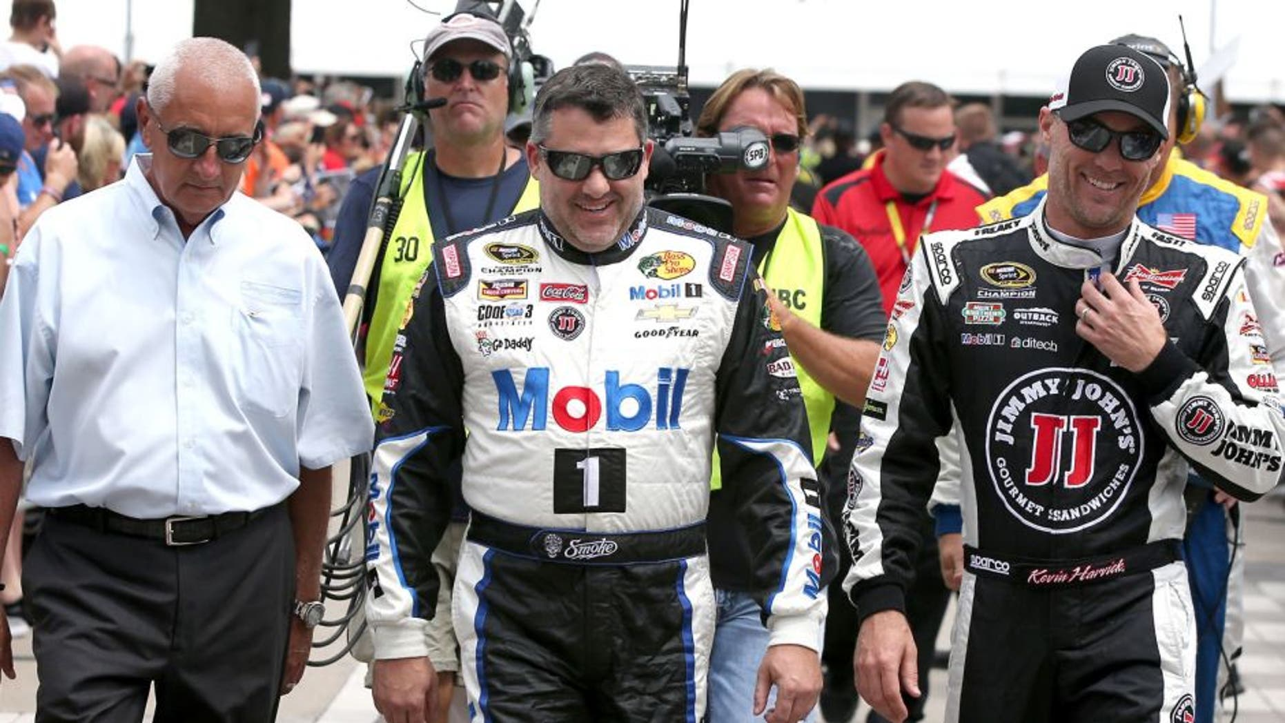 INDIANAPOLIS, IN - JULY 26: Tony Stewart, driver of the #14 Mobil 1/Bass Pro Shops Chevrolet, and Kevin Harvick, driver of the #4 Jimmy John's/Budweiser Chevrolet, walk along The Yard of Bricks prior to being introduced for the NASCAR Sprint Cup Series Crown Royal Presents the Jeff Kyle 400 at the Brickyard at Indianapolis Motor Speedway on July 26, 2015 in Indianapolis, Indiana. (Photo by Sean Gardner/NASCAR via Getty Images)