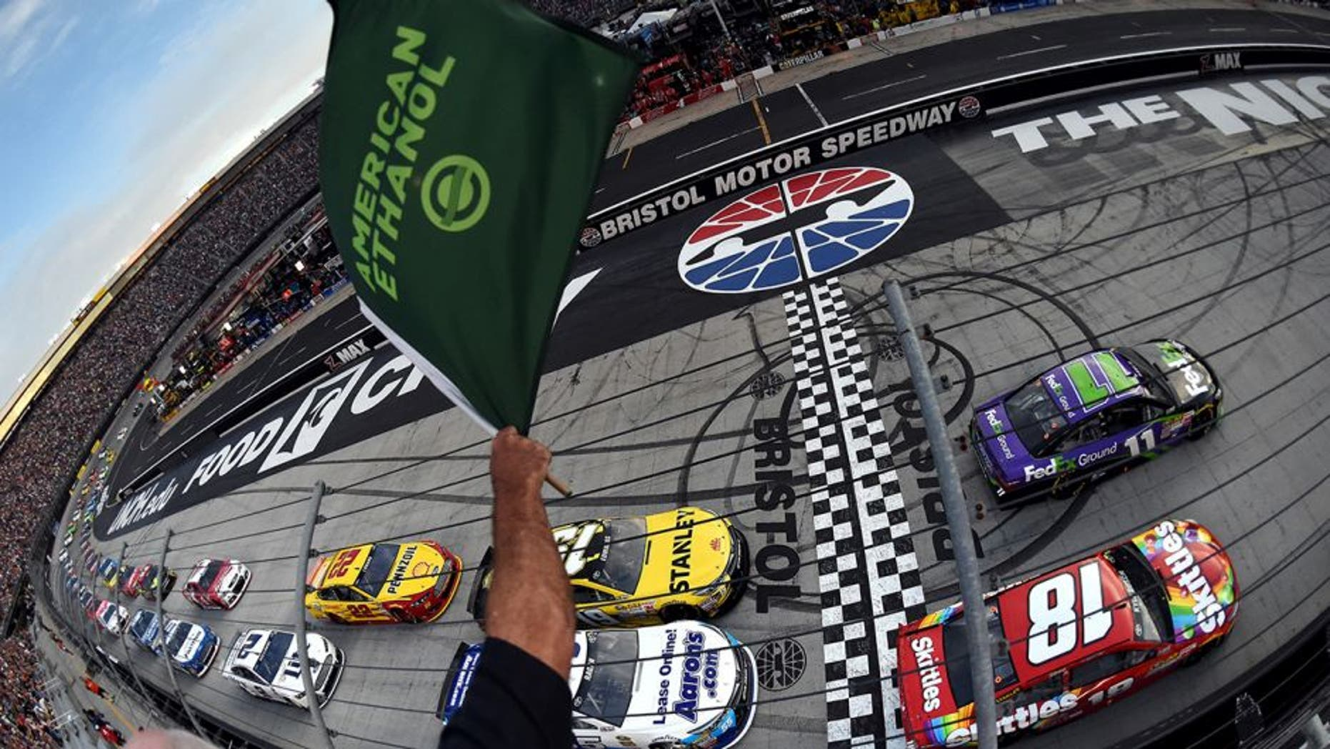 BRISTOL, TN - AUGUST 22: Denny Hamlin, driver of the #11 FedEx Ground Toyota, and Kyle Busch, driver of the #18 Skittles Toyota, lead the field through the green flag to start the NASCAR Sprint Cup Series IRWIN Tools Night Race at Bristol Motor Speedway on August 22, 2015 in Bristol, Tennessee. (Photo by Rainier Ehrhardt/NASCAR via Getty Images)