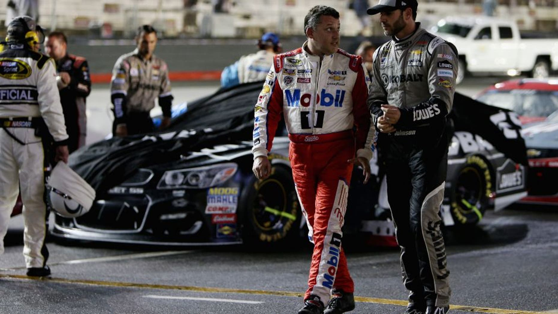 BRISTOL, TN - AUGUST 20: Tony Stewart, driver of the #14 Haas Automation Chevrolet, walks on the grid with Jimmie Johnson, driver of the #48 Kobalt Chevrolet, during a rain delay during the NASCAR Sprint Cup Series Bass Pro Shops NRA Night Race at Bristol Motor Speedway on August 20, 2016 in Bristol, Tennessee. (Photo by Rey Del Rio/Getty Images)