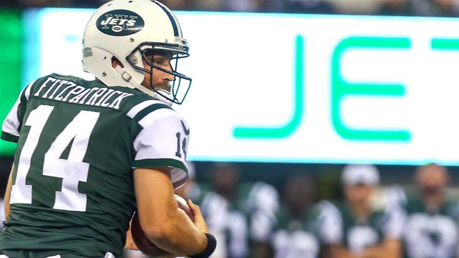 Aug 21, 2015; East Rutherford, NJ, USA; New York Jets quarterback Ryan Fitzpatrick (14) runs with the ball during the first half at MetLife Stadium. Mandatory Credit: Ed Mulholland-USA TODAY Sports