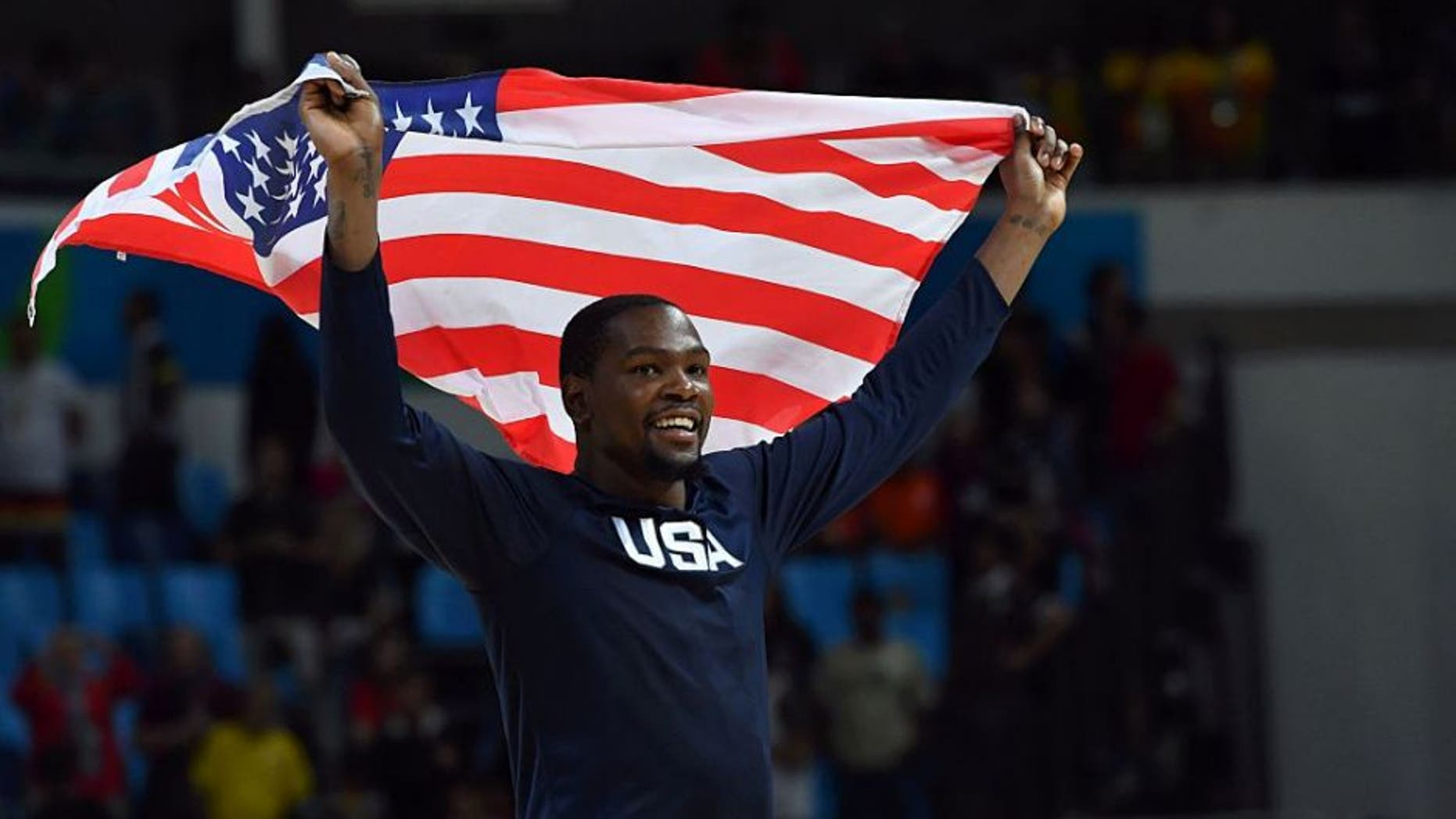 USA's guard Kevin Durant celebrates with USA's flag after defeating Serbia during a Men's Gold medal basketball match between Serbia and USA at the Carioca Arena 1 in Rio de Janeiro on August 21, 2016 during the Rio 2016 Olympic Games. / AFP / Andrej ISAKOVIC (Photo credit should read ANDREJ ISAKOVIC/AFP/Getty Images)