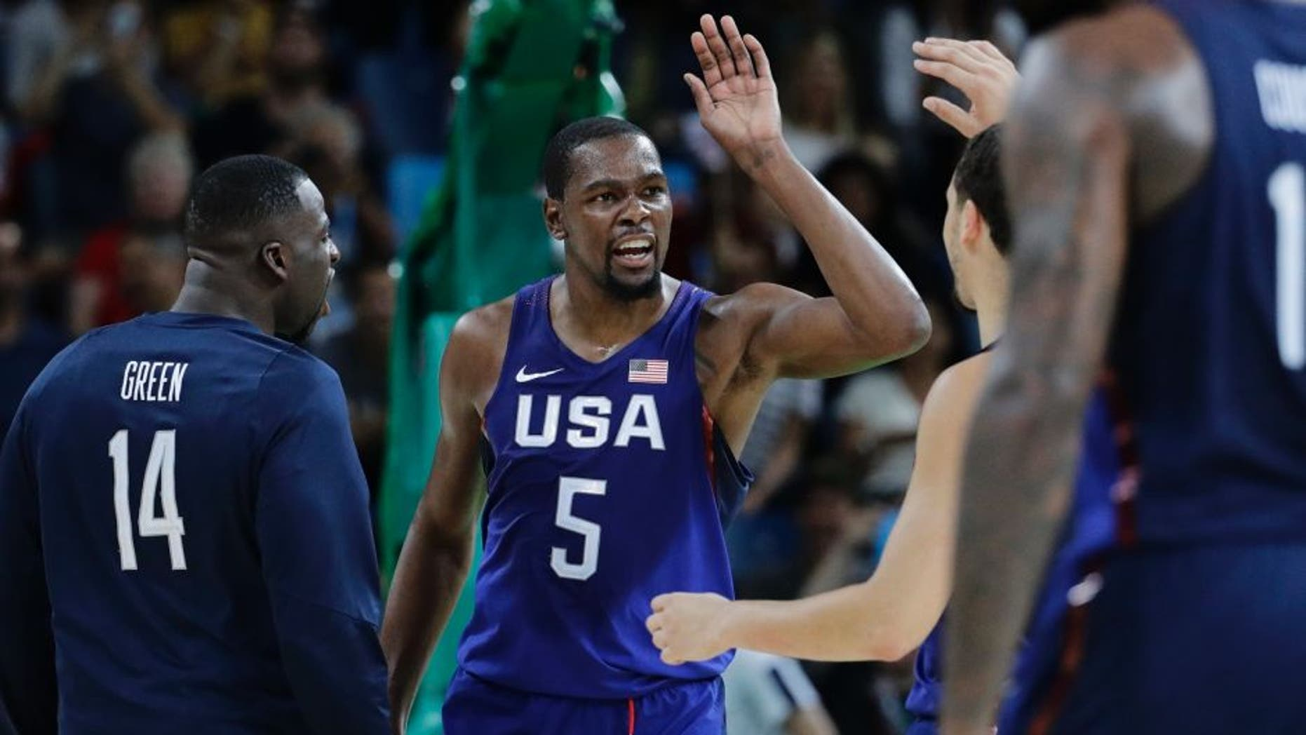United States' Kevin Durant (5) celebrates with teammates United States' Draymond Green (14) and others after a steal and dunk against Serbia during the men's gold medal basketball game at the 2016 Summer Olympics in Rio de Janeiro, Brazil, Sunday, Aug. 21, 2016. (AP Photo/Matt York)