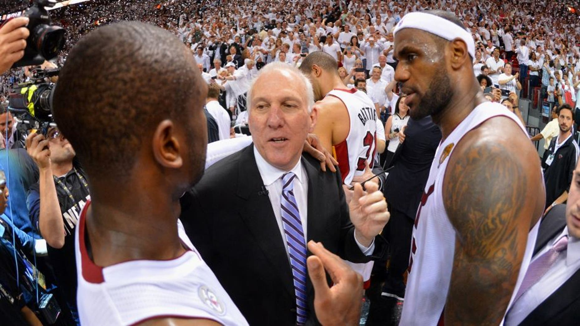 MIAMI, FL - JUNE 20: Gregg Popovich of the San Antonio Spurs congratulates Dwyane Wade #3 and LeBron James #6 of the Miami Heat in Game Seven of the 2013 NBA Finals on June 20, 2013 at American Airlines Arena in Miami, Florida. NOTE TO USER: User expressly acknowledges and agrees that, by downloading and or using this photograph, User is consenting to the terms and conditions of the Getty Images License Agreement. Mandatory Copyright Notice: Copyright 2013 NBAE (Photo by Jesse D. Garrabrant/NBAE via Getty Images)