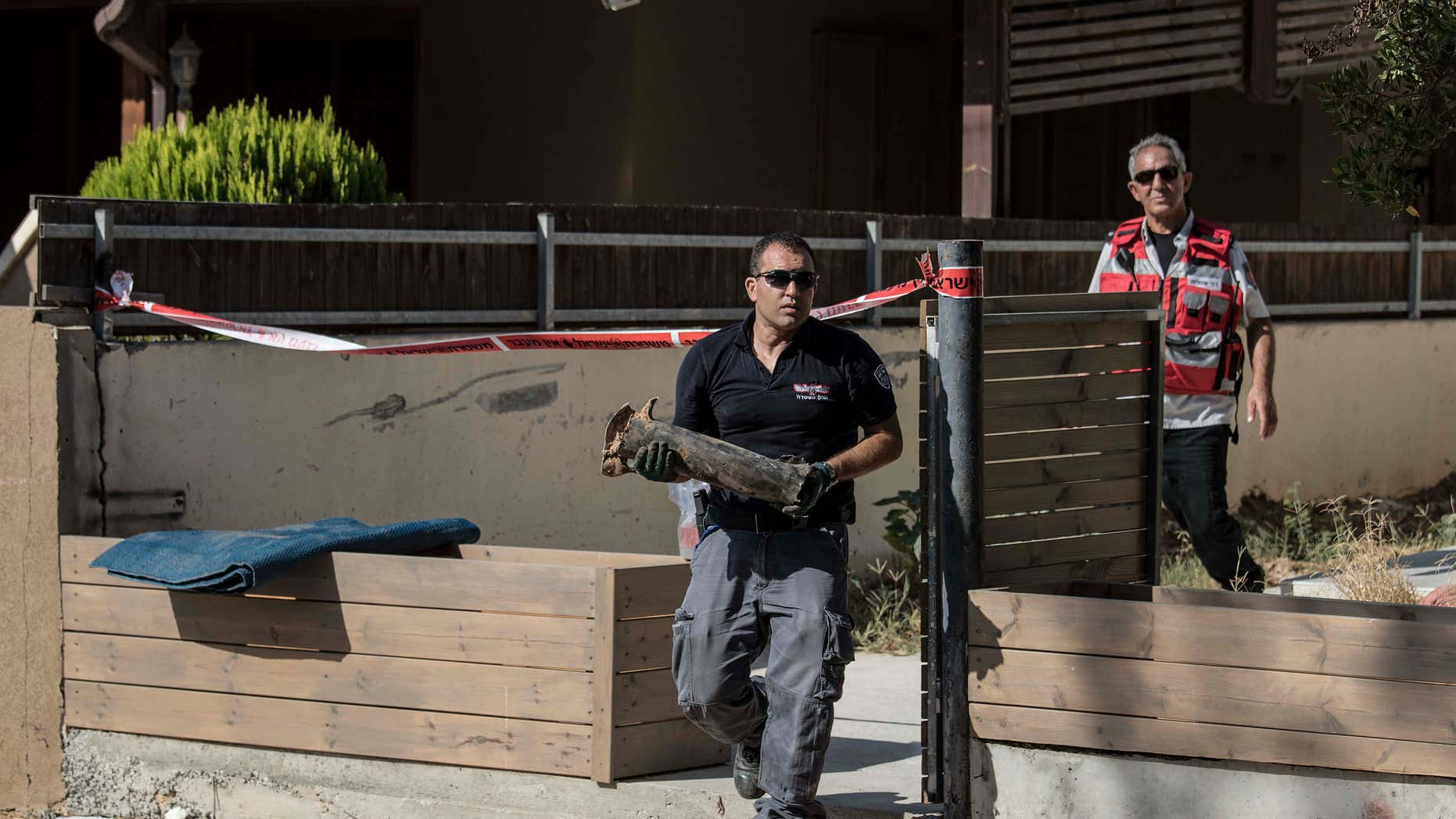 Aug. 21, 2016: An Israeli police sapper carries part of a rocket which landed in a yard of a house in the city of Sderot, southern Israel.