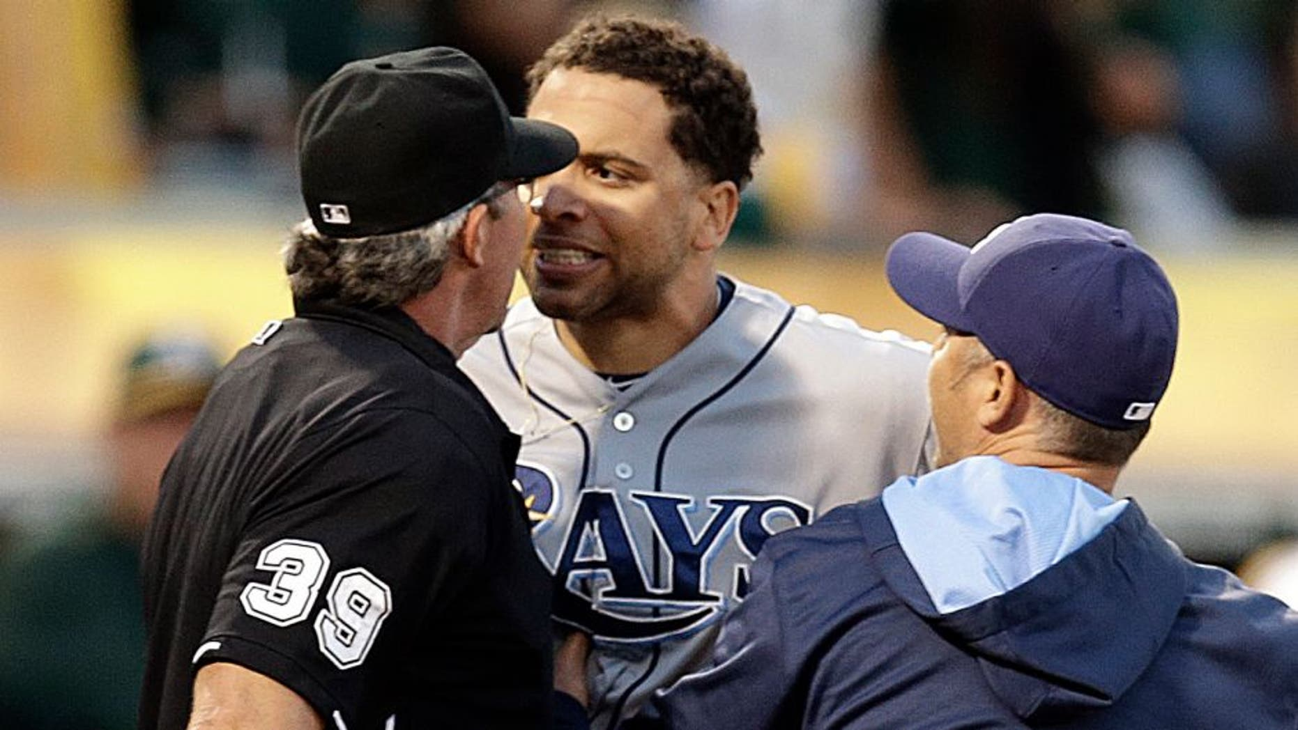 Tampa Bay Rays' James Loney, center, is restrained by manager Kevin Cash, right, while arguing with home plate umpire Paul Nauert (39) after being ejected in the sixth inning of a baseball game against the Oakland Athletics, Saturday, Aug. 22, 2015, in Oakland, Calif. (AP Photo/Ben Margot)