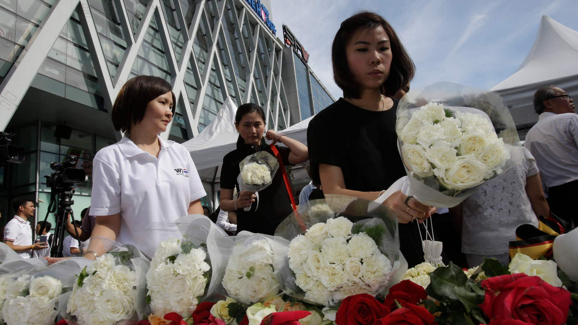 Aug. 21, 2015: People leave flowers at a shopping plaza across from the Erawan Shrine at Rajprasong intersection, the scene of Monday's bombing, for a multi-denominational religious service for victims in Bangkok, Thailand