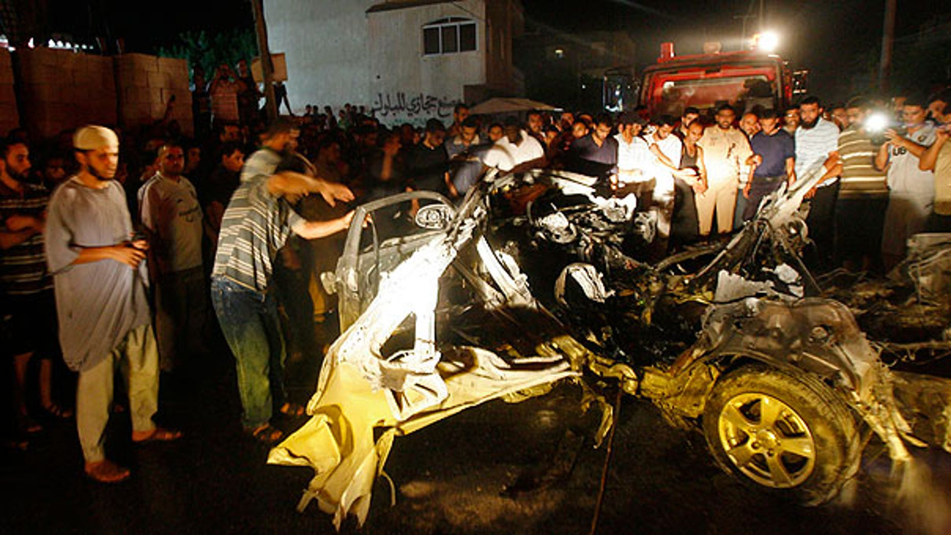 Aug. 24: Palestinians look at the wreckage of a car after it was hit by an Israeli missile, killing an Islamic Jihad militant in Rafah, southern Gaza Strip.