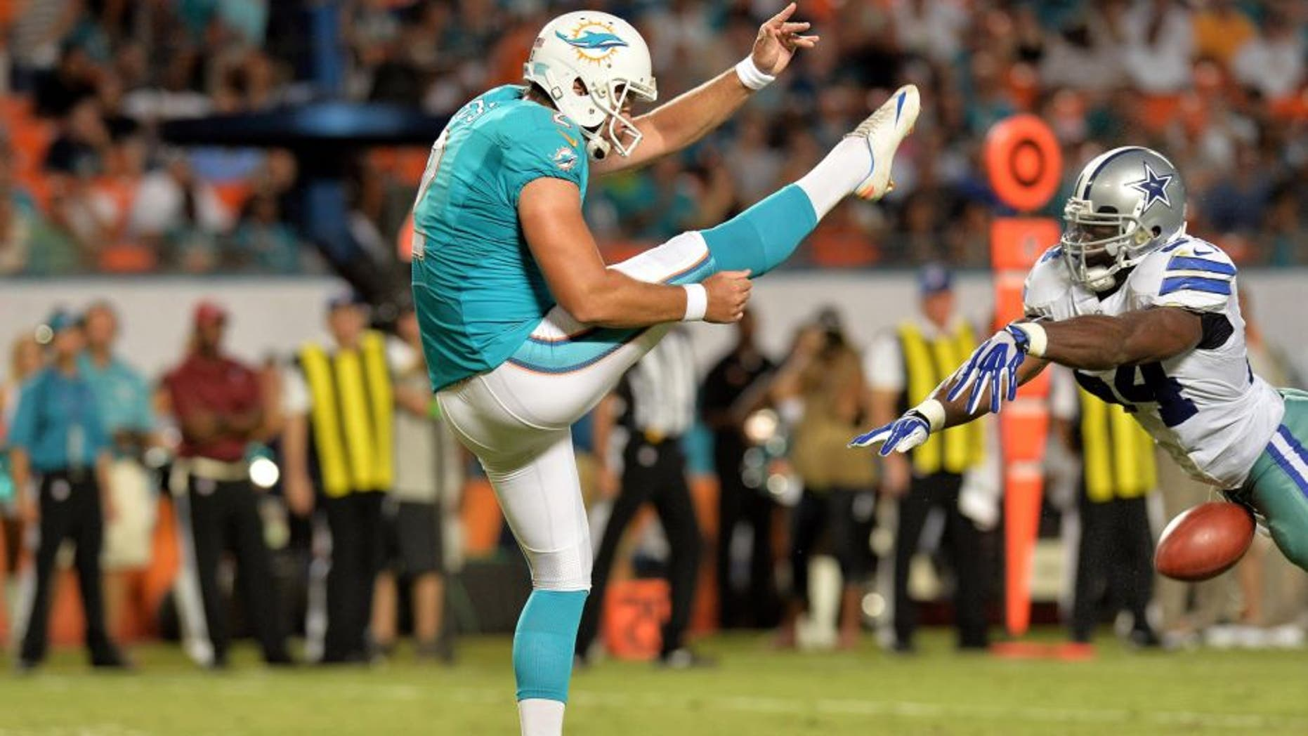 Aug 23, 2014; Miami Gardens, FL, USA; Dallas Cowboys outside linebacker Bruce Carter (54) blocks the punt of Miami Dolphins punter Brandon Fields (2) during the first half at Sun Life Stadium. Mandatory Credit: Steve Mitchell-USA TODAY Sports