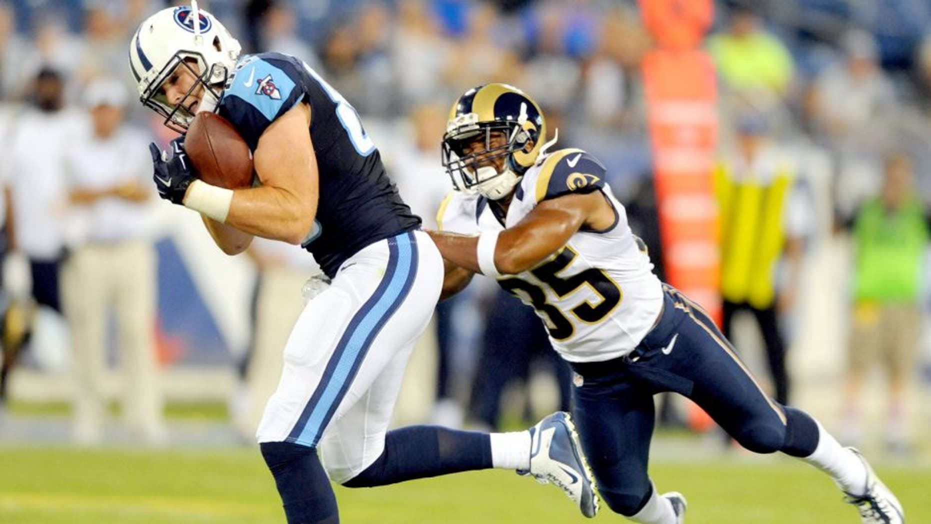 Aug 23, 2015; Nashville, TN, USA; Tennessee Titans tight end Chase Coffman (85) catches a touchdown pass while being defended by St. Louis Rams safety Jay Hughes (35) during the second half at Nissan Stadium. The Titans won 27-14. Mandatory Credit: Christopher Hanewinckel-USA TODAY Sports