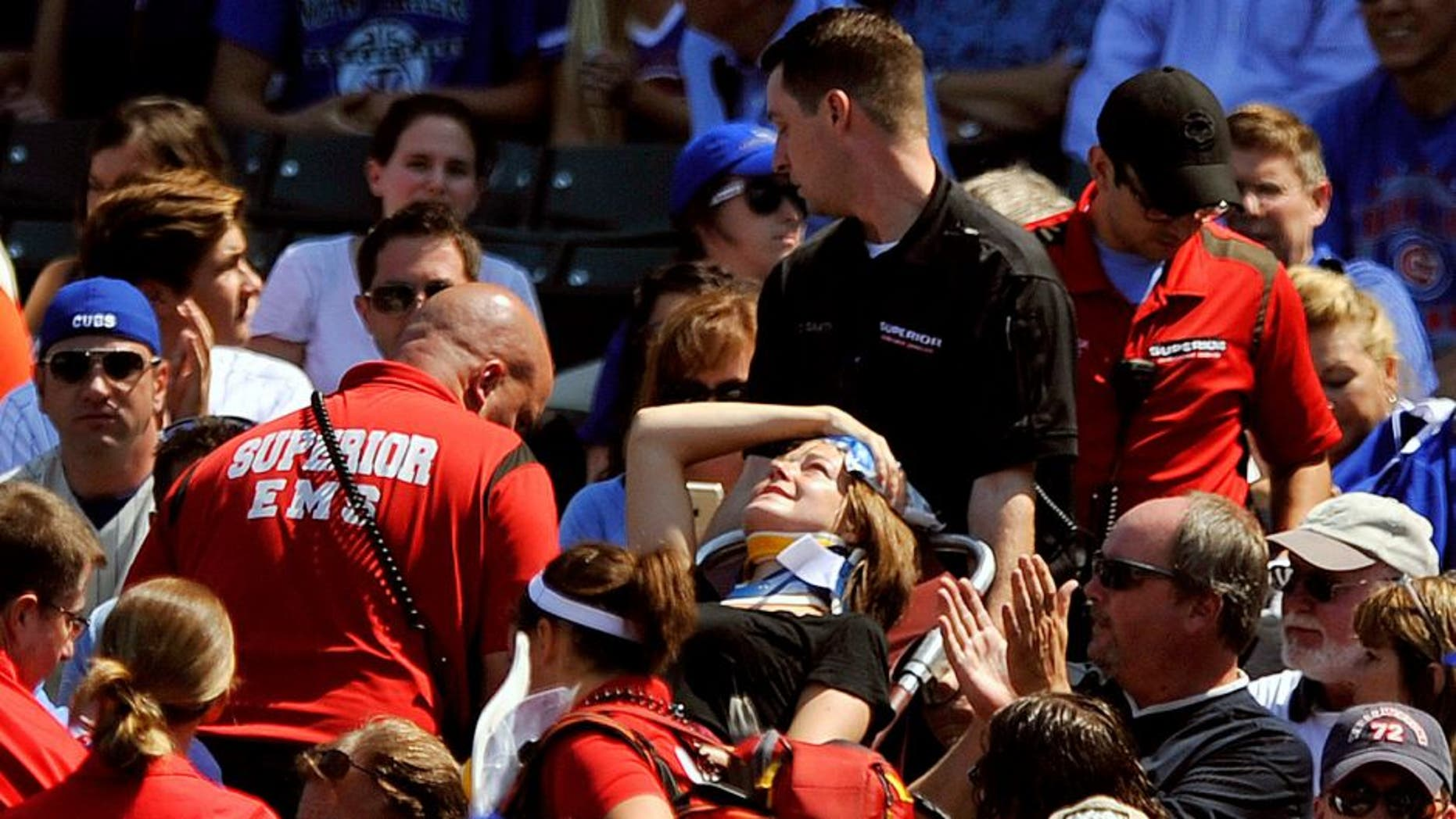 A fan is carried away after being hit a by a line-drive foul ball during the first inning of a baseball game between the Chicago Cubs and the Atlanta Braves at Wrigley Field, Sunday, Aug. 23, 2015, in Chicago. (AP Photo/Paul Beaty)