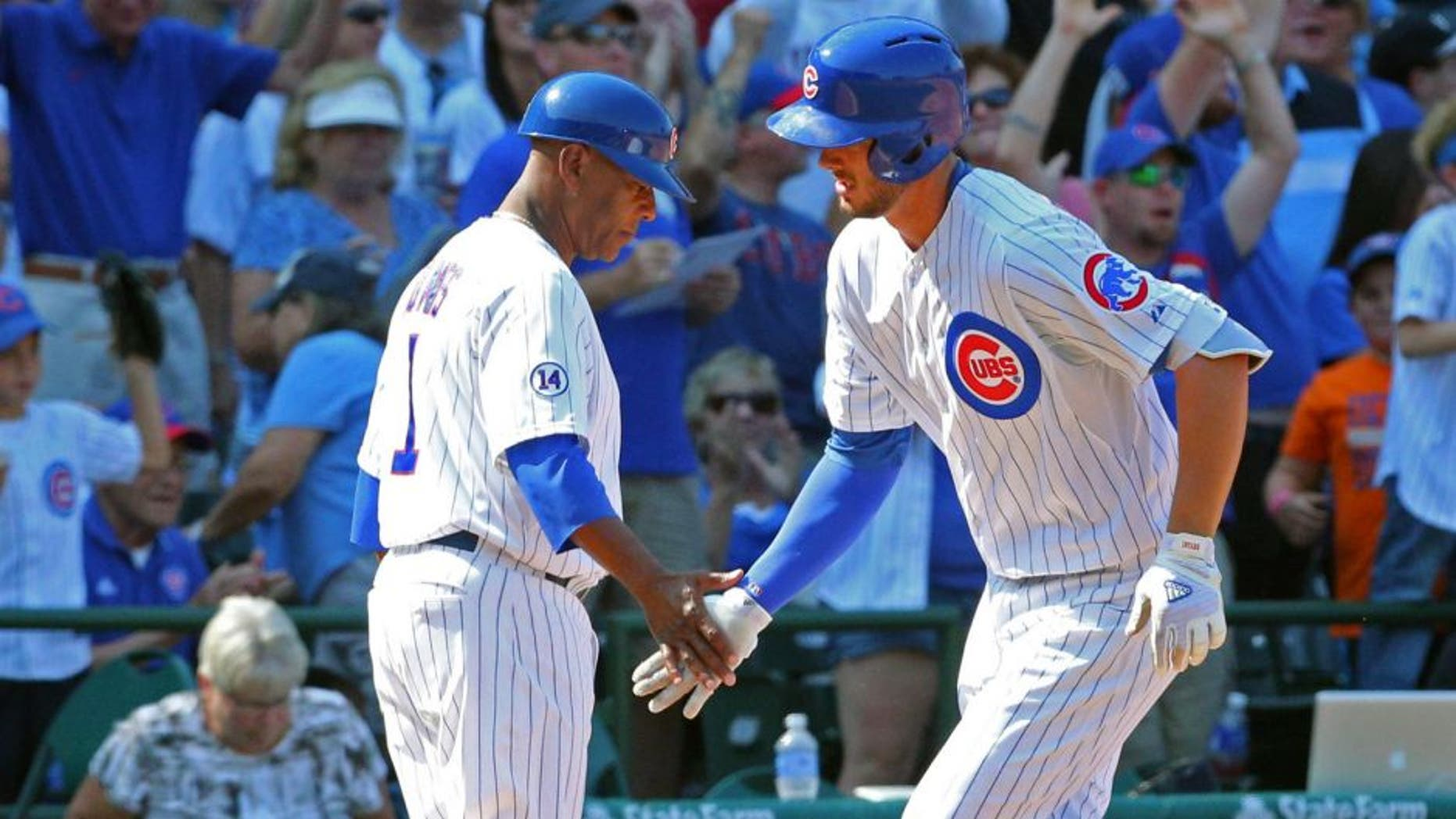 Aug 23, 2015; Chicago, IL, USA; Chicago Cubs third baseman Kris Bryant (17) is congratulated for hitting a home run by third base coach Gary Jones (1) during the sixth inning against the Atlanta Braves at Wrigley Field. Mandatory Credit: Dennis Wierzbicki-USA TODAY Sports