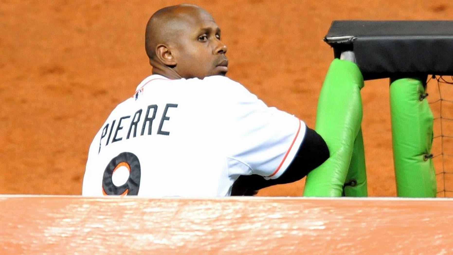 Sep 9, 2013; Miami, FL, USA; Miami Marlins left fielder Juan Pierre (9) looks on from the dugout during the third inning against the Atlanta Braves at Marlins Park. Mandatory Credit: Steve Mitchell-USA TODAY Sports