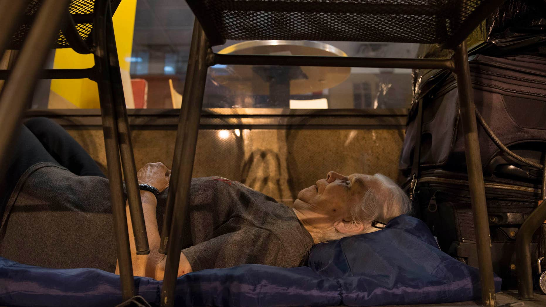 In this Aug. 10, 2016 photo, with suitcases in arms reach, homeless woman Wanda Witter beds down in her sleeping spot outside the Au Bon Pain on 13th and G Street in Washington, DC Witter, who is 80 years old, was recently attacked at the location suffering a black eye and two stitches.