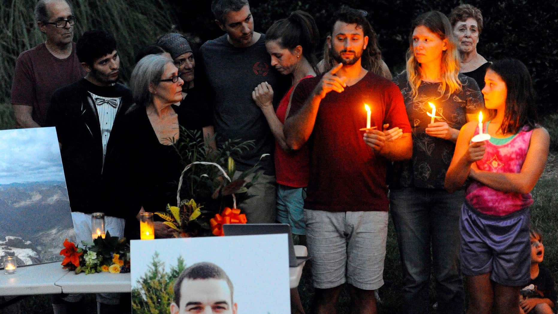 Aug. 22, 2016: Sam Harris, center, older brother of Daniel Harris signs to the crowd during a candlelight vigil along Seven Oaks Drive to remember Daniel Harris.