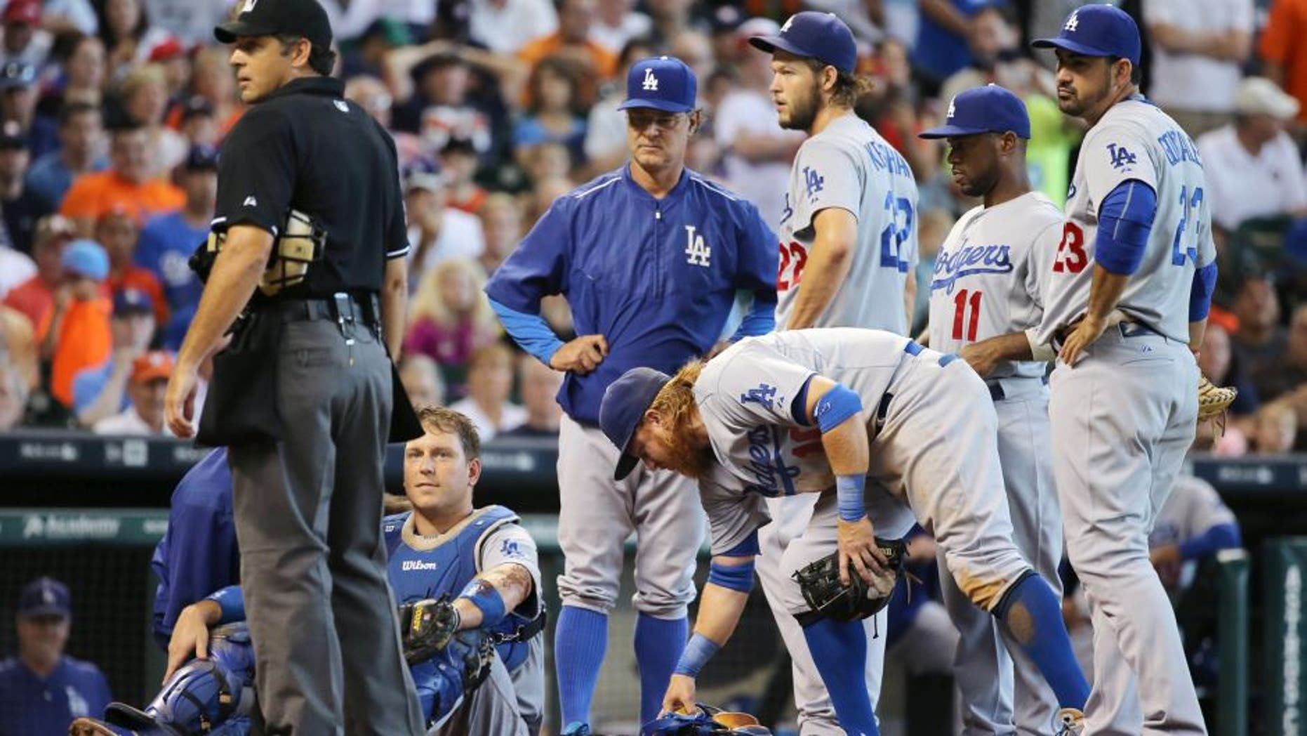 HOUSTON, TX - AUGUST 23: Catcher A.J. Ellis #17 of the Los Angeles Dodgers sits on the ground after a tough slide by Carlos Gomez #30 of the Houston Astros in the sixth inning during their game at Minute Maid Park on August 23, 2015 in Houston, Texas. (Photo by Scott Halleran/Getty Images)