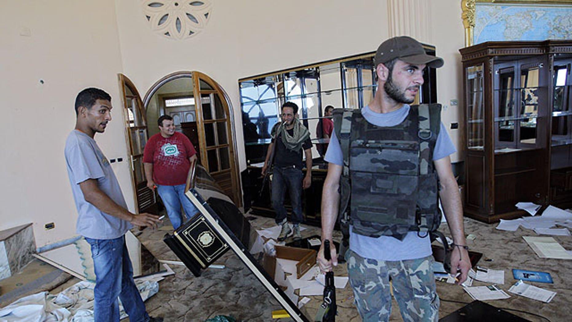 August 24: A rebel fighter walks inside the house of Al-Saadi Qaddafi, the son of Libyan dictator Muammar Qaddafi in Tripoli, Libya,