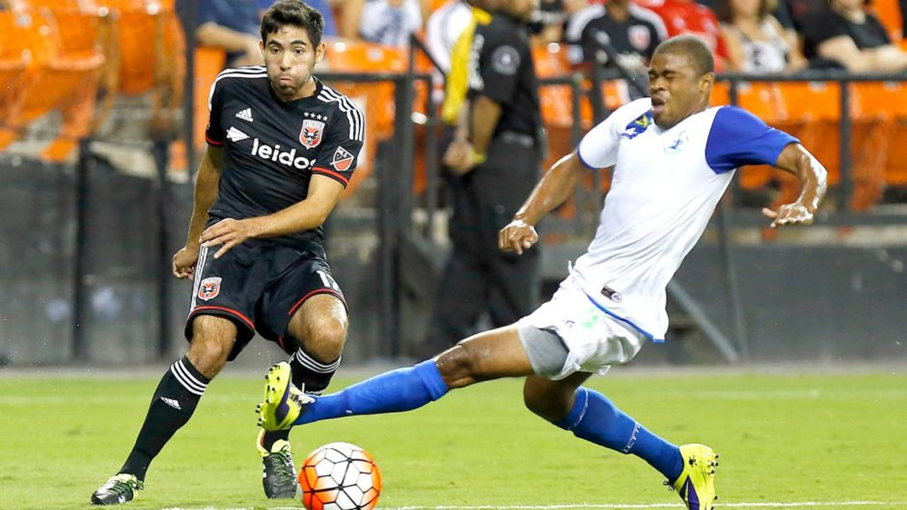 Aug 25, 2015; Washington, DC, USA; D.C. United midfielder Miguel Aguilar (17) passes the ball as Montego Bay F.C. defender Dwayne Holmes (5) defends in the first half at RFK Stadium. United won 3-0. Mandatory Credit: Geoff Burke-USA TODAY Sports