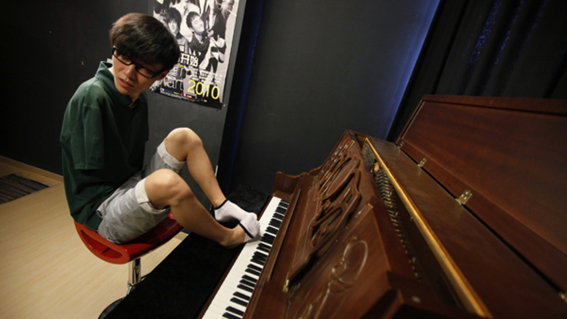 Aug. 26: Pianist Liu Wei takes off one of his socks to play piano in Shanghai. The 23-year-old's arms were amputated after a childhood accident.