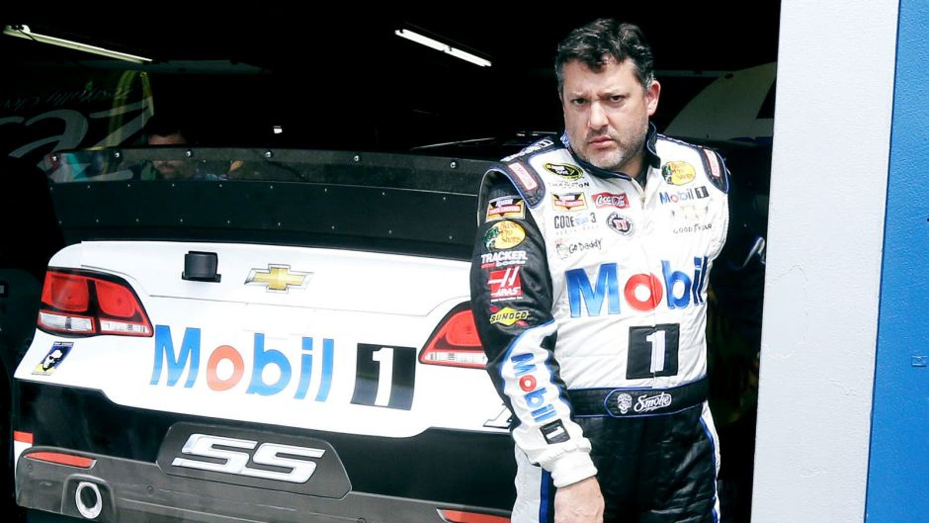 Tony Stewart leaves the garage after a practice session Friday, Aug. 14, 2015, for Sunday's NASCAR Sprint Cup series auto race at Michigan International Speedway in Brooklyn, Mich. (AP Photo/Carlos Osorio)