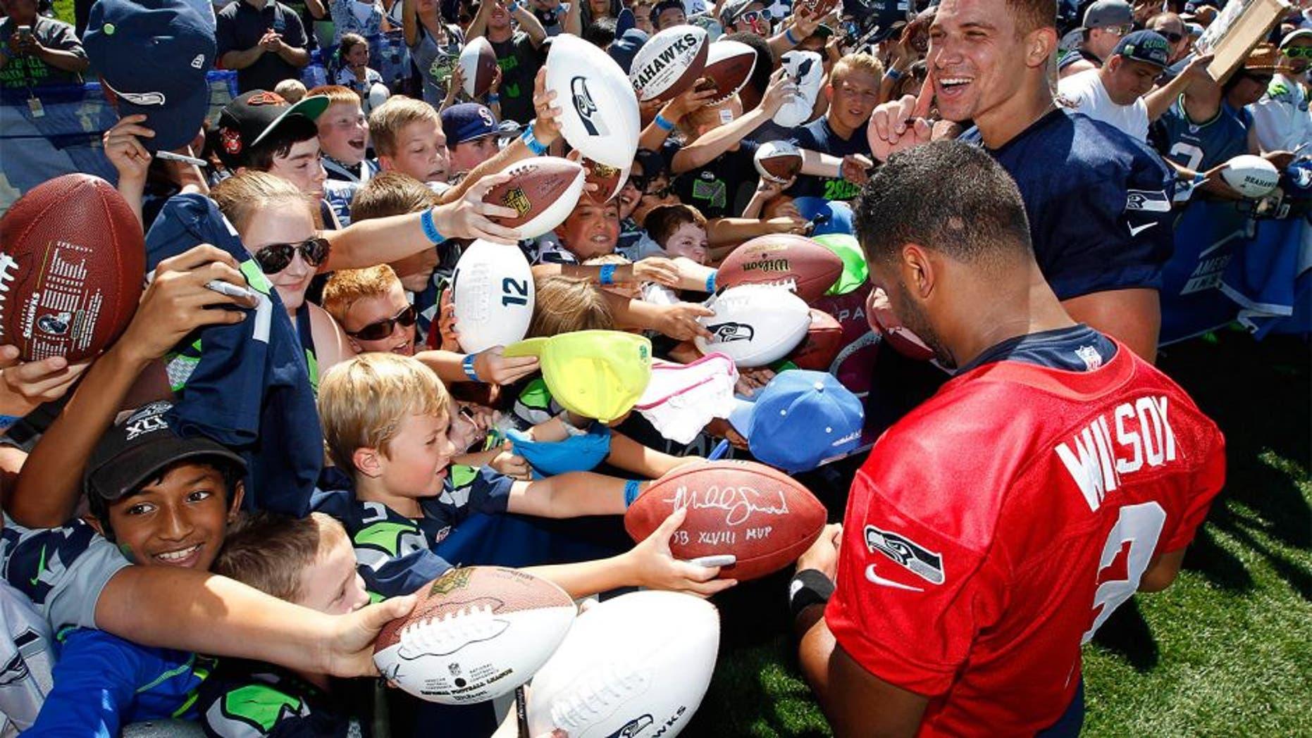 Jul 31, 2015; Renton, WA, USA; Seattle Seahawks quarterback Russell Wilson (3) and tight end Jimmy Graham (88) sign autographs following training camp practice at Virginia Mason Athletic Center. Mandatory Credit: Joe Nicholson-USA TODAY Sports